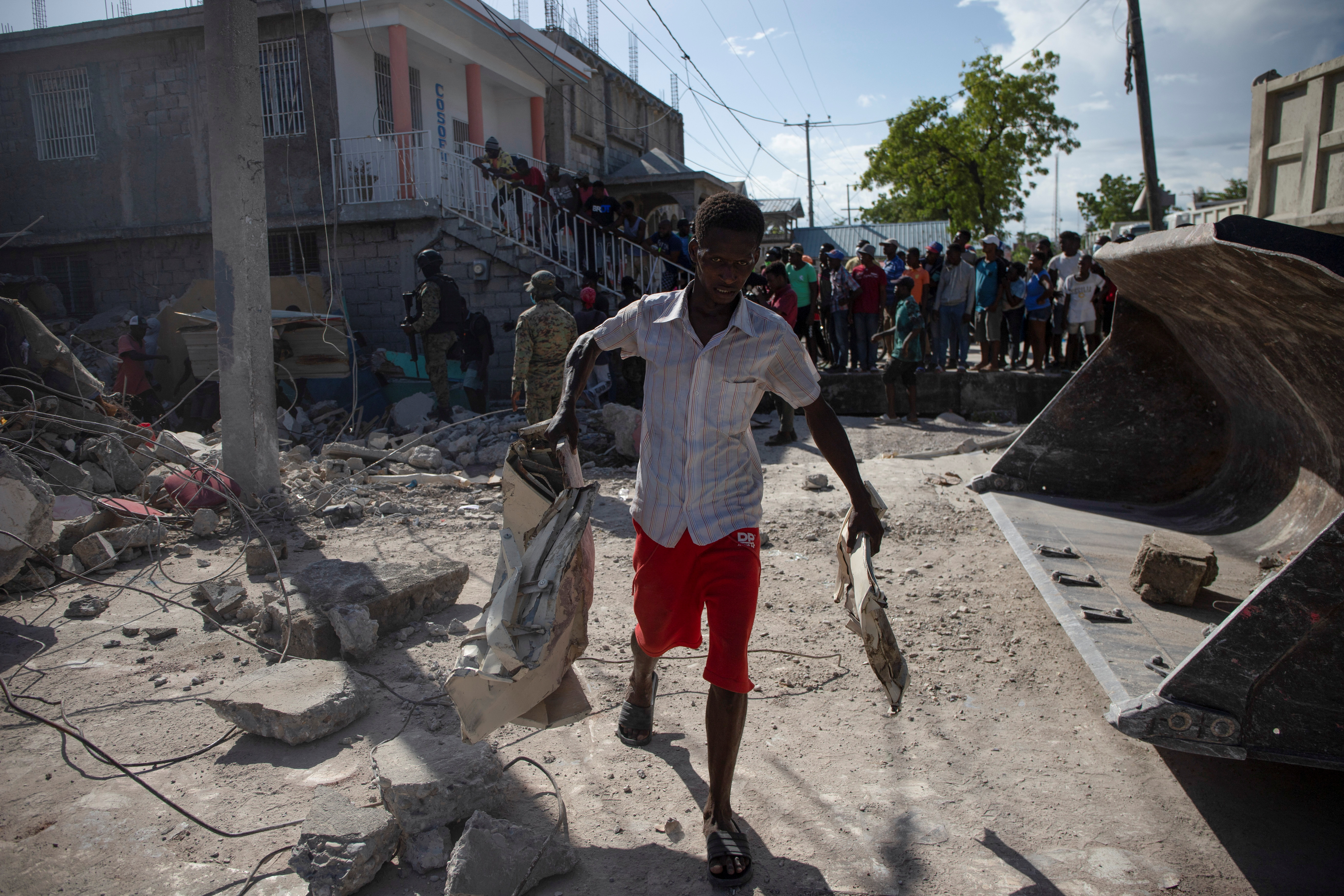 A man removes debris from a house after a 7.2 magnitude earthquake in Les Cayes, Haiti August 15, 2021.  REUTERS/Estailove St-Val