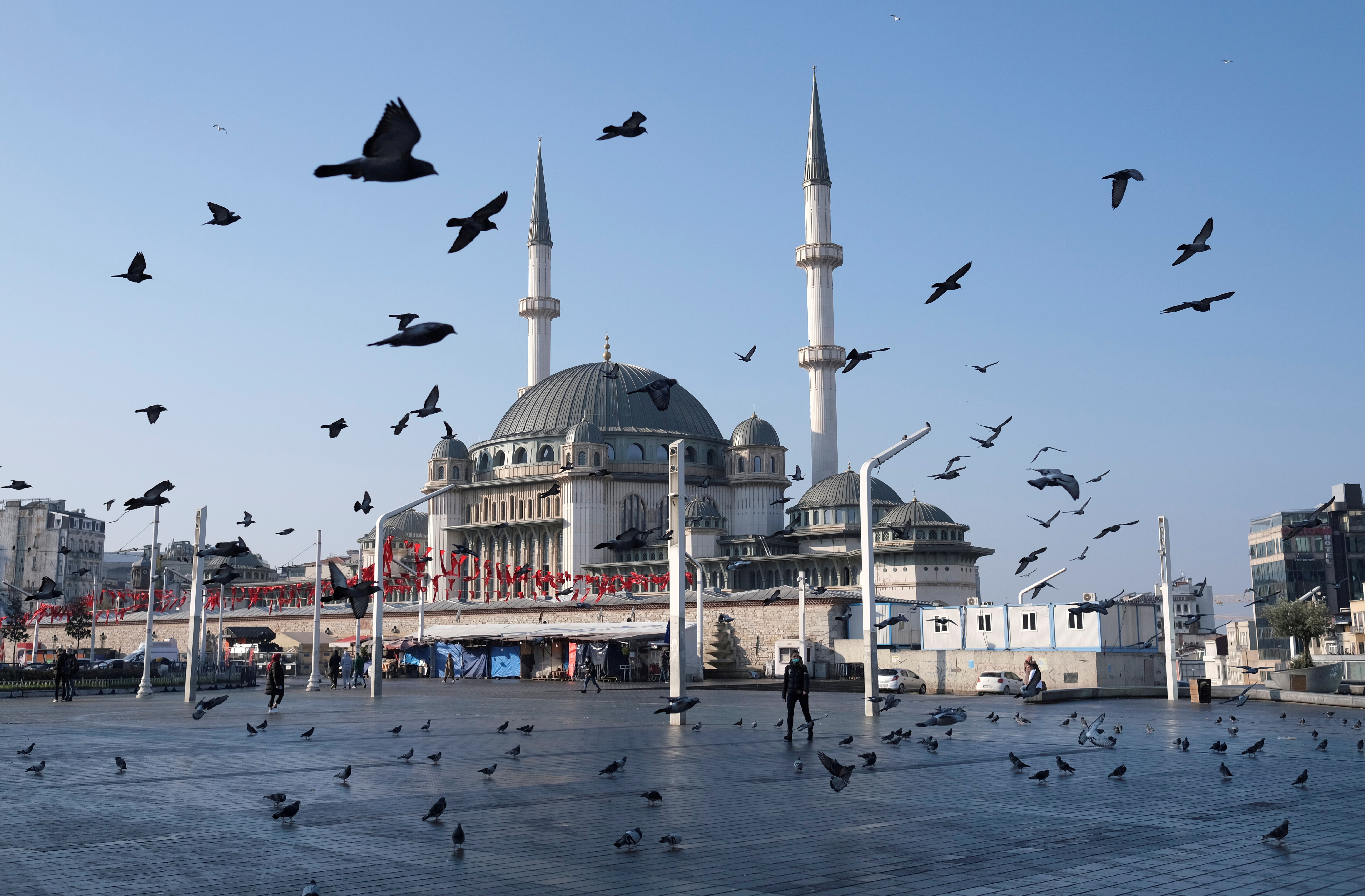 Pigeons fly over the Taksim Square during a nation-wide weekend curfew which was imposed to prevent the spread of the coronavirus disease (COVID-19), in Istanbul, Turkey December 5, 2020. REUTERS/Murad Sezer