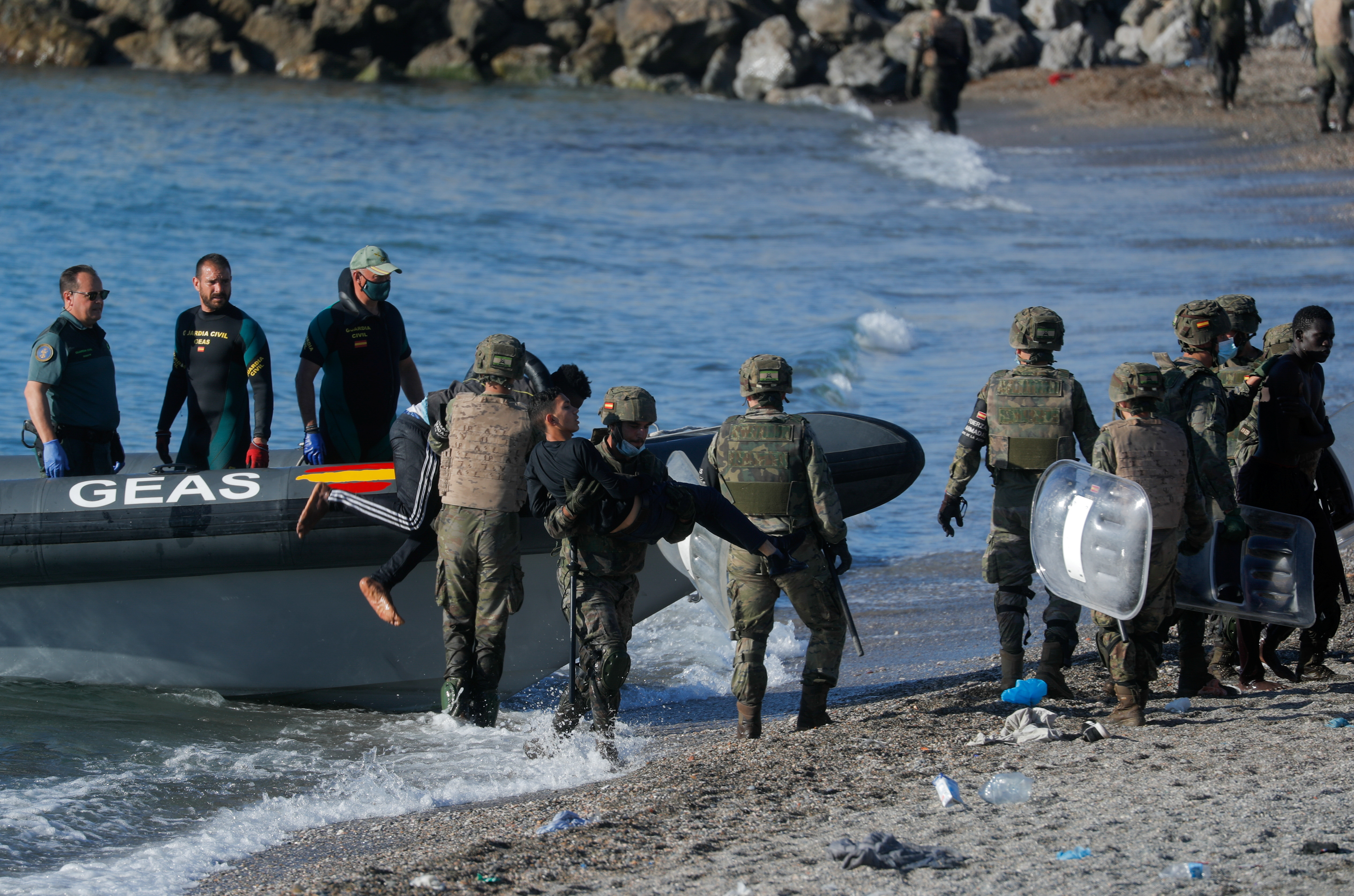 Spanish soldiers help Moroccan citizens at El Tarajal beach, near the fence between the Spanish-Moroccan border, after thousands of migrants swam across the border, in Ceuta, Spain, May 19, 2021. REUTERS/Jon Nazca