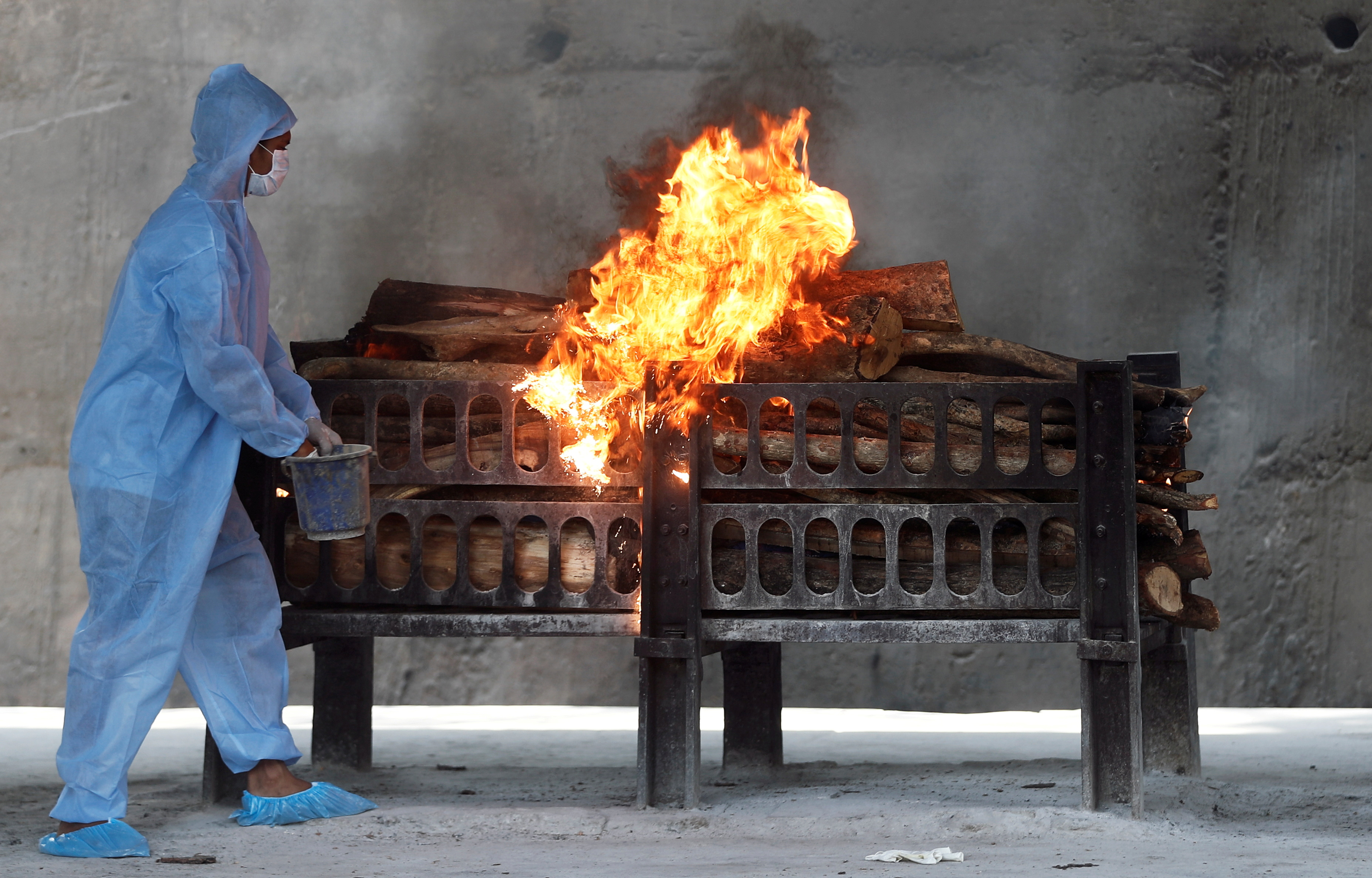 A frontline worker in personal protective equipment (PPE) sprays a flammable liquid on a burning funeral pyre of a man who died from the coronavirus disease  (COVID-19), at a crematorium on the outskirts of Mumbai India, April 15, 2021. REUTERS/Francis Mascarenhas/File Photo