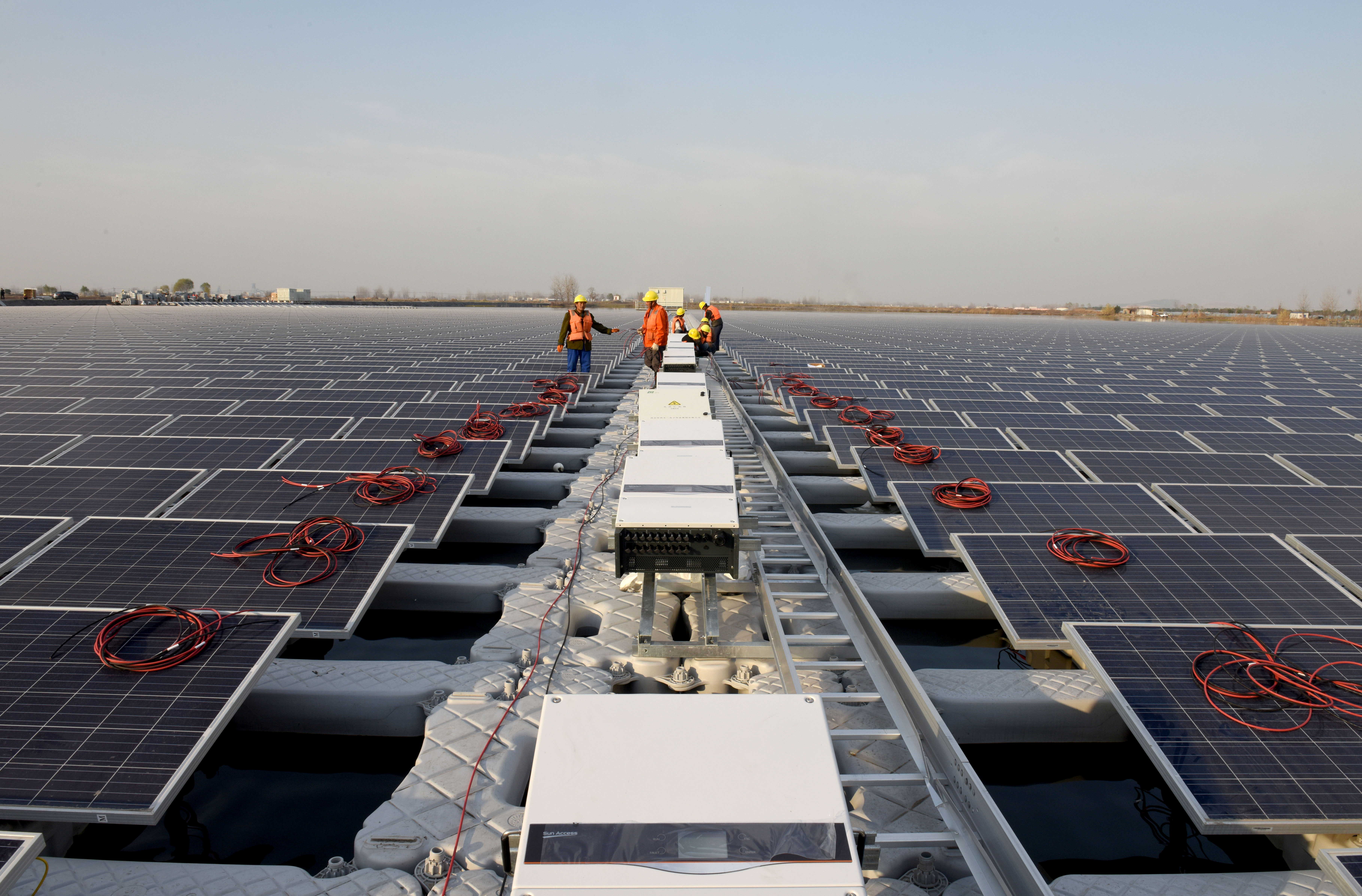 Workers install solar panels at a floating solar plant developed by China's Three Gorges Group, in Huainan, Anhui province, China December 11, 2017. Picture taken December 11, 2017. REUTERS/Stringer