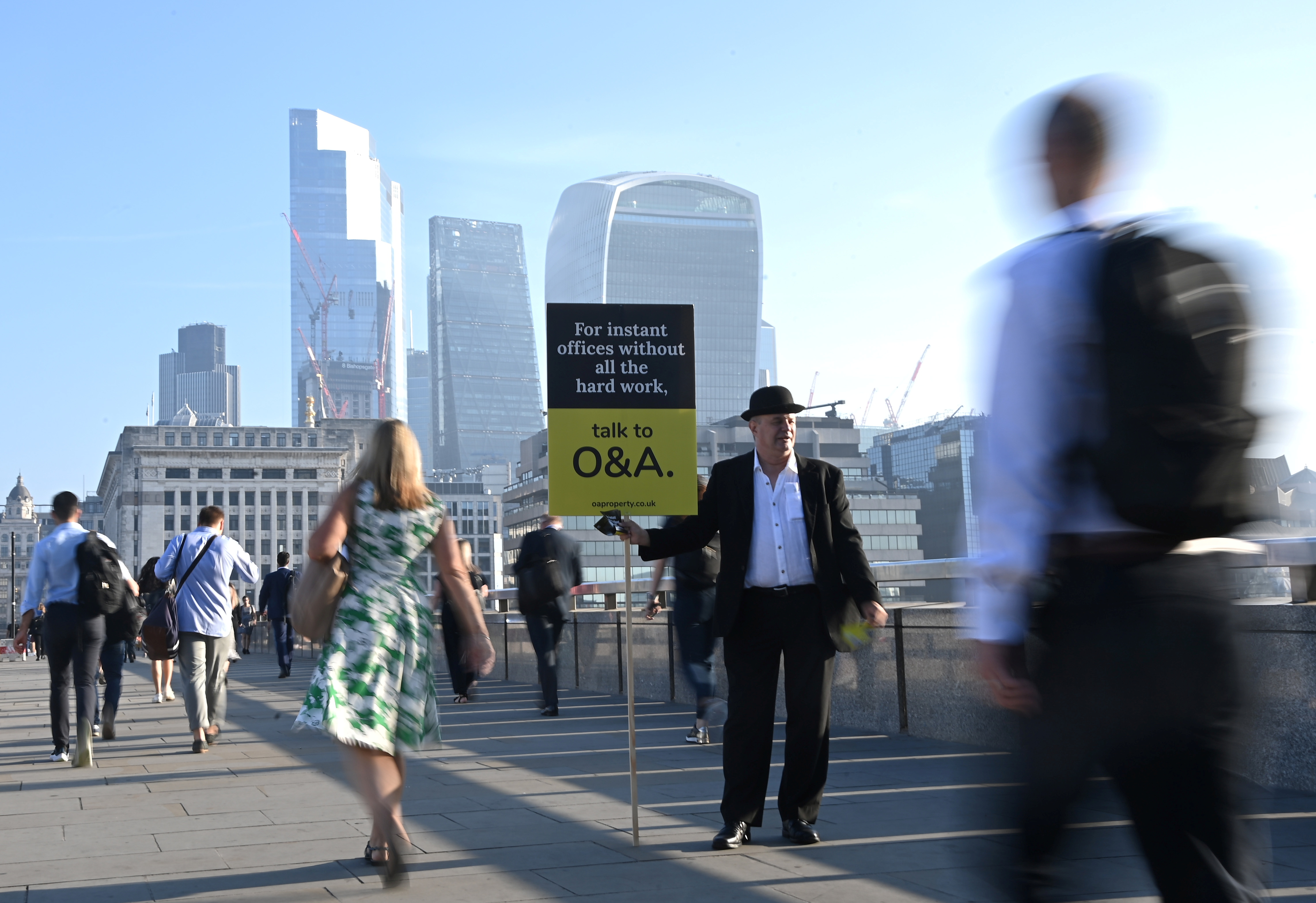 Workers pass by a sales person as they walk towards the City of London financial district as they cross London Bridge during the morning rush hour in London, Britain, September 8, 2021. REUTERS/Toby Melville