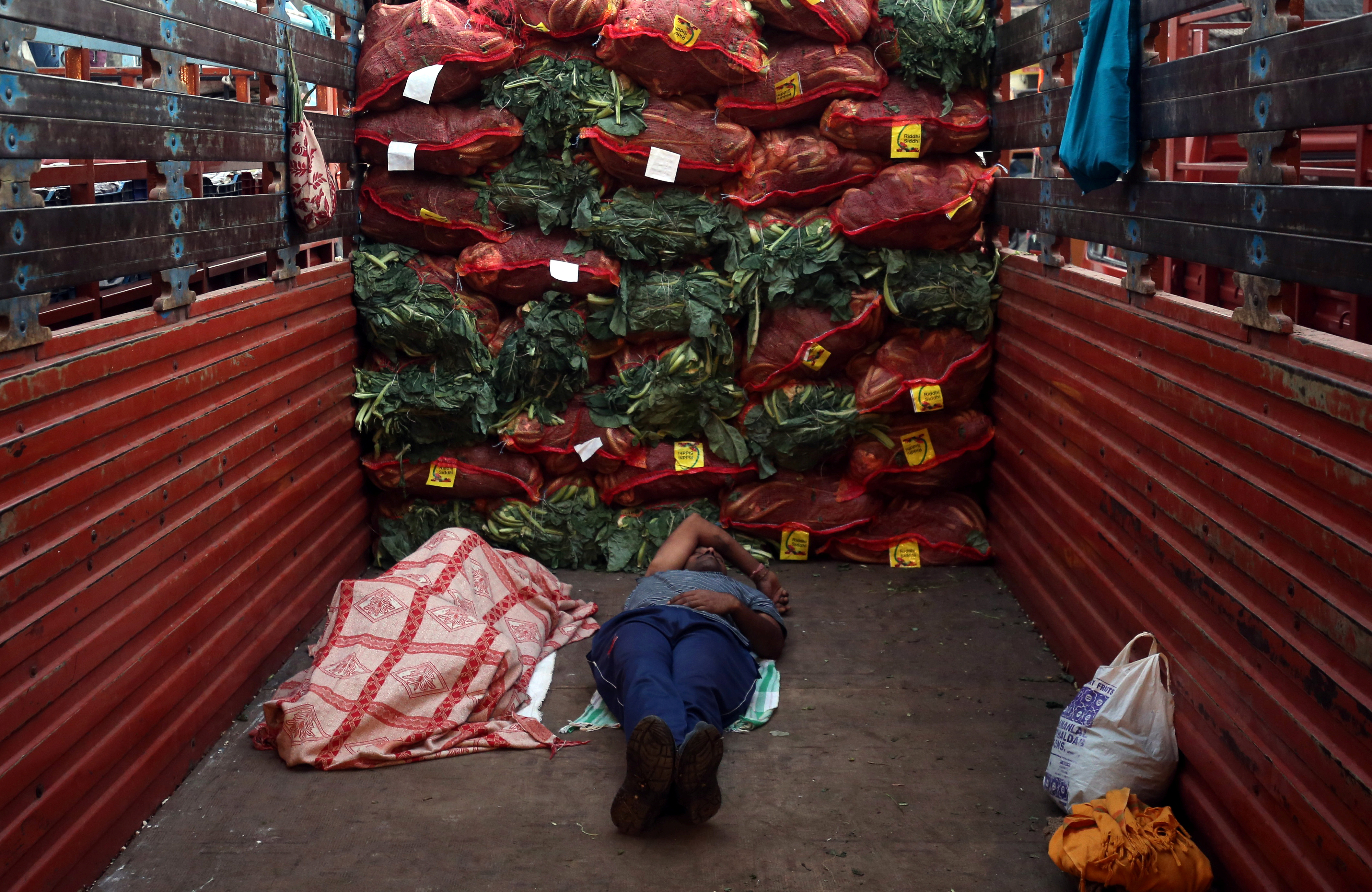 Men sleep in a supply truck loaded with sacks of cauliflower at a vegetable wholesale market in Mumbai, India, February 14, 2019. REUTERS/Francis Mascarenhas