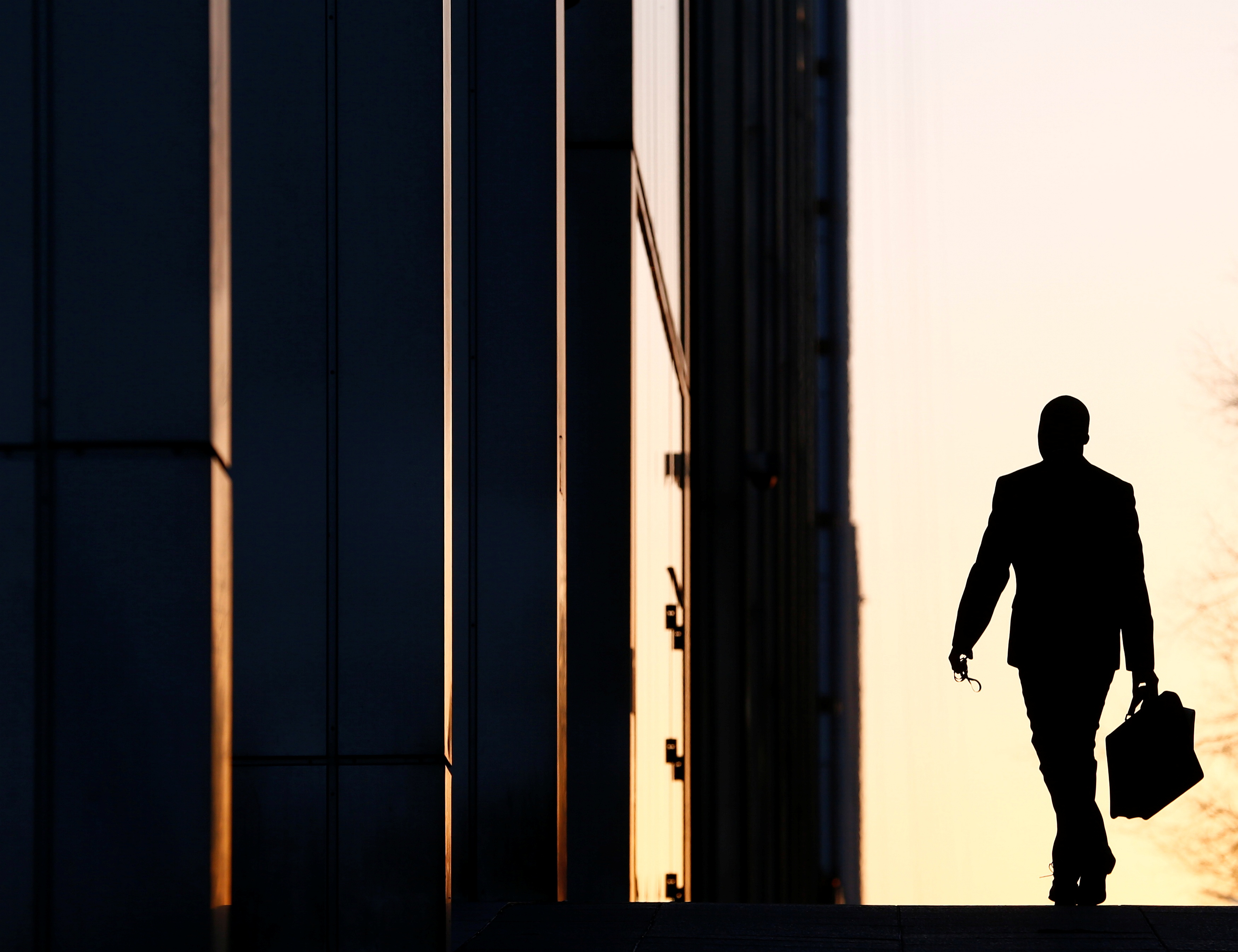 A worker arrives at his office in the Canary Wharf business district in London February 26, 2014./File Photo
