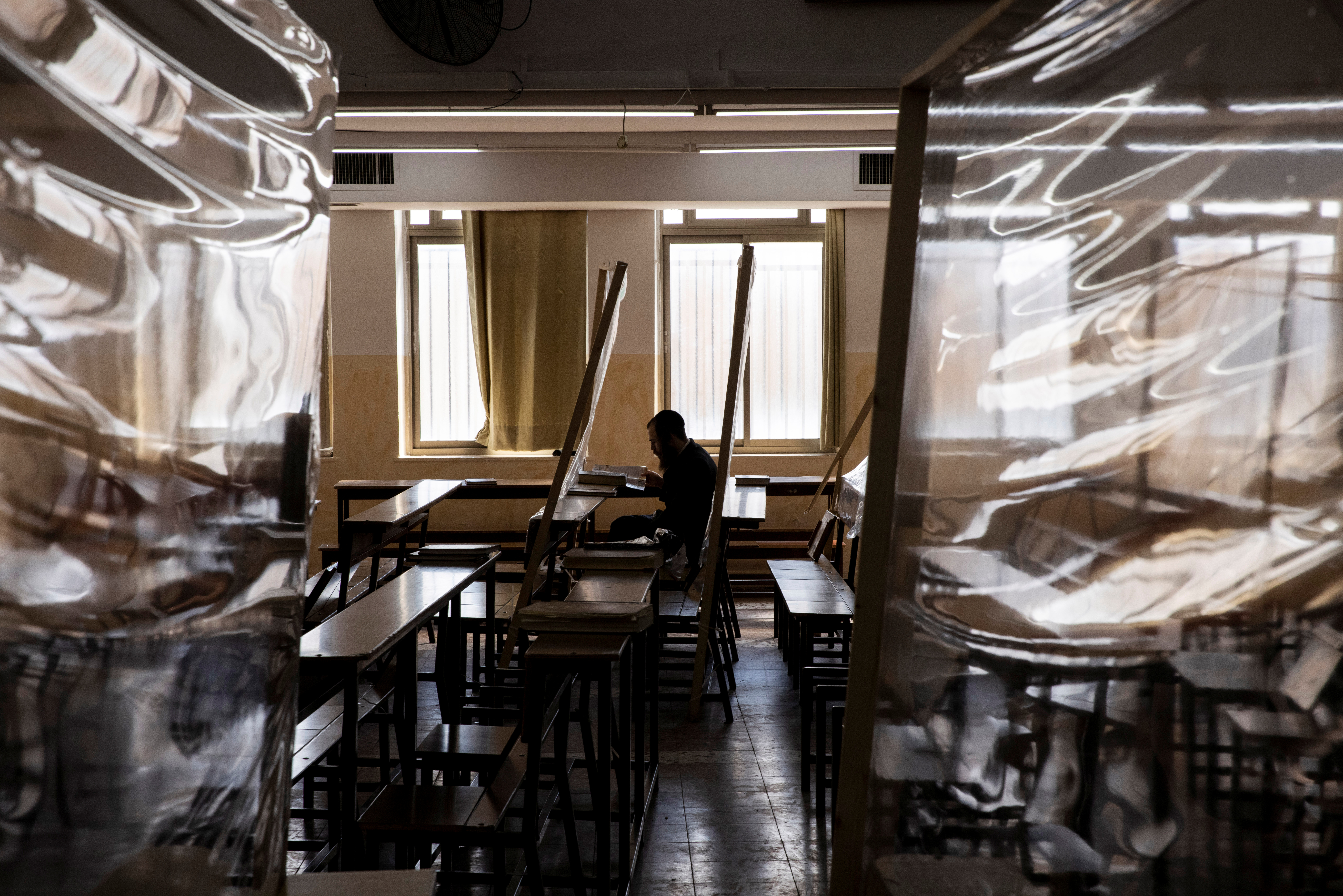 An ultra-Orthodox Jewish man studies in a Yeshiva, or Jewish seminary, equipped with partitions to protect against the spread of the coronavirus disease (COVID-19), in the Mea Shearim neighbourhood of Jerusalem March 2, 2021. Picture taken March 2, 2021. REUTERS/Ronen Zvulun