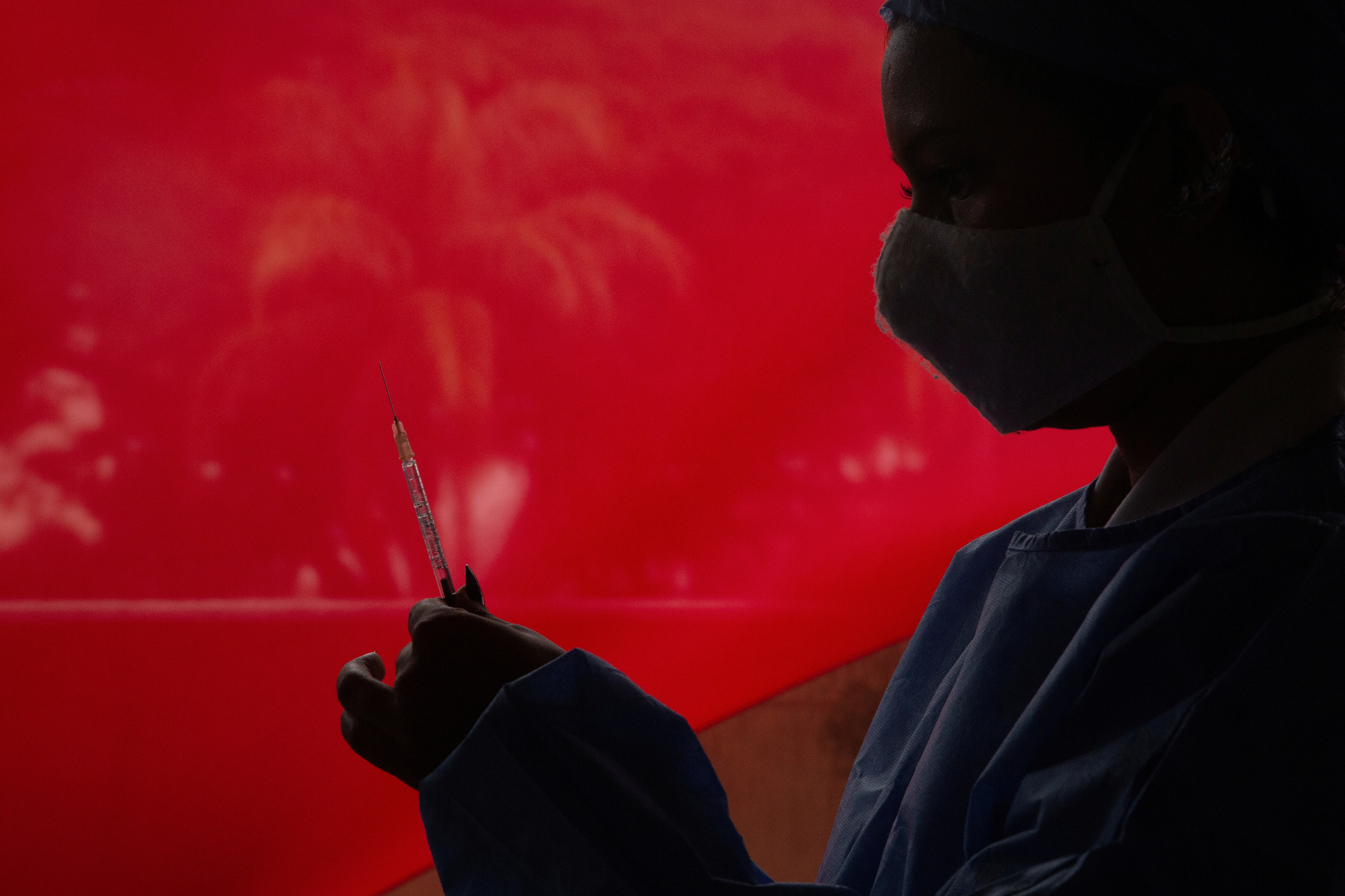 A healthcare worker prepares a dose of Russia's Sputnik V vaccine against the coronavirus disease (COVID-19), in the parking lot of the Social Security Institute of the Armed Forces, turned into a mass vaccination centre, in Caracas, Venezuela June 5, 2021. REUTERS/Leonardo Fernandez Viloria