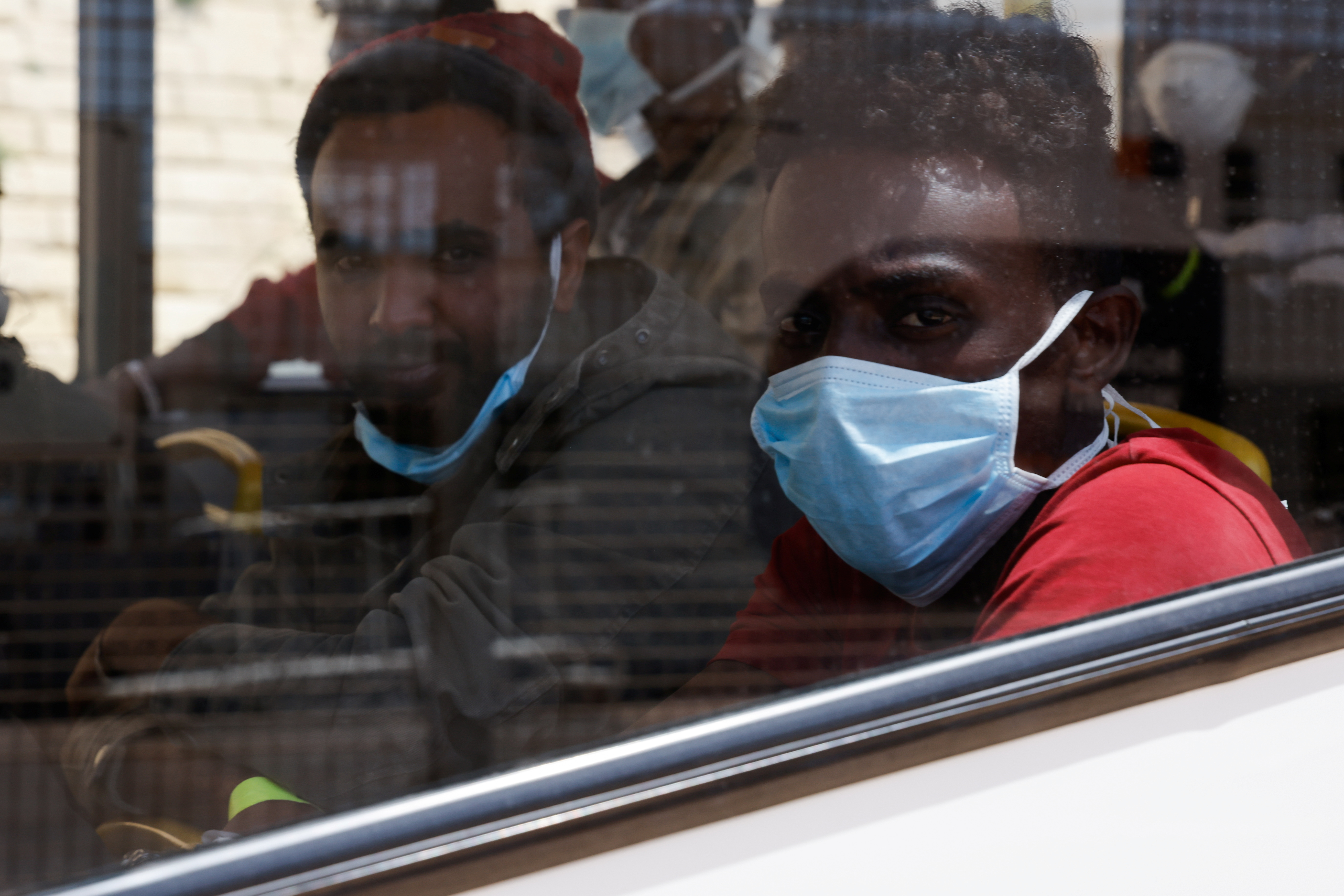 Rescued migrants sit after disembarking from an Armed Forces of Malta vessel in Senglea, in Valletta's Grand Harbour, as the coronavirus disease (COVID-19) outbreak continues in Malta May 11, 2021. REUTERS/Darrin Zammit Lupi