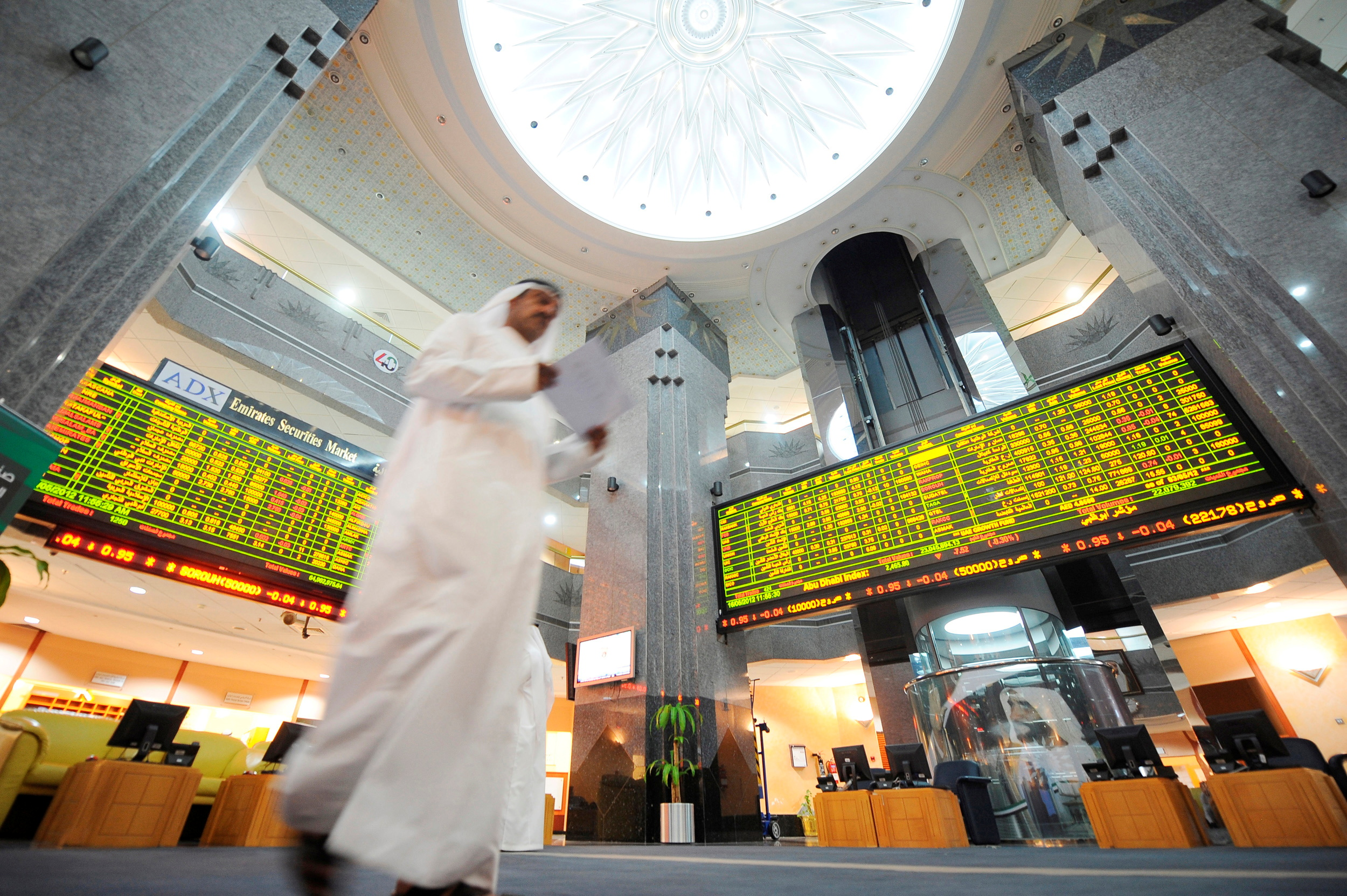Electronic boards displaying stock information are seen as an investor walks past at the ADX Abu Dhabi Securities Exchange stock market May 16, 2012. REUTERS/Ben Job/File Photo