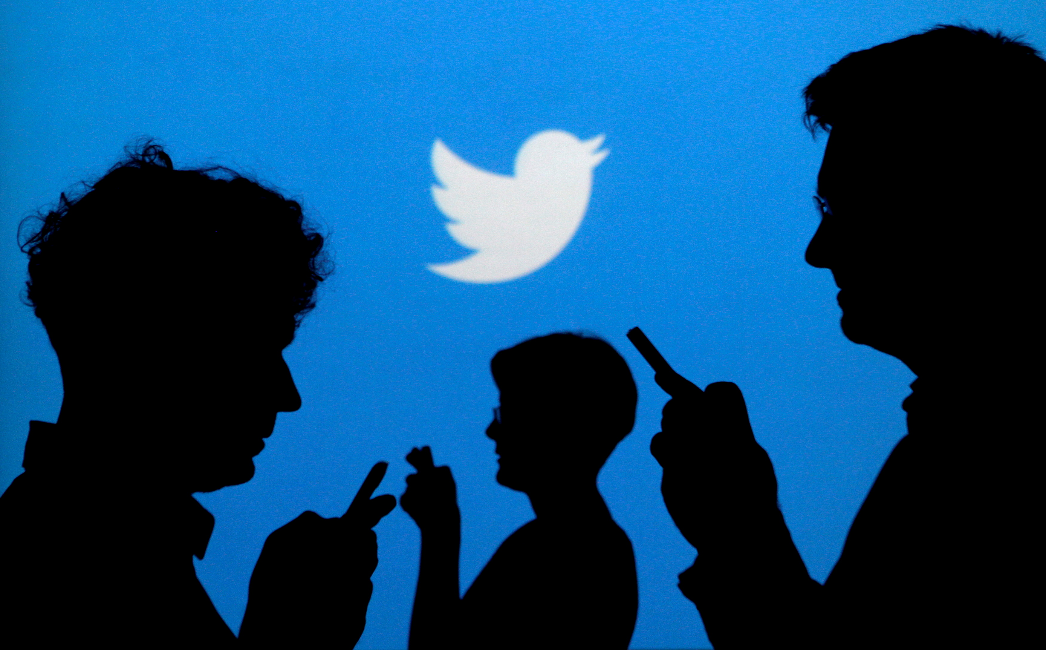 People holding mobile phones are silhouetted against a backdrop projected with the Twitter logo in this illustration. REUTERS/Kacper Pempel/Illustration