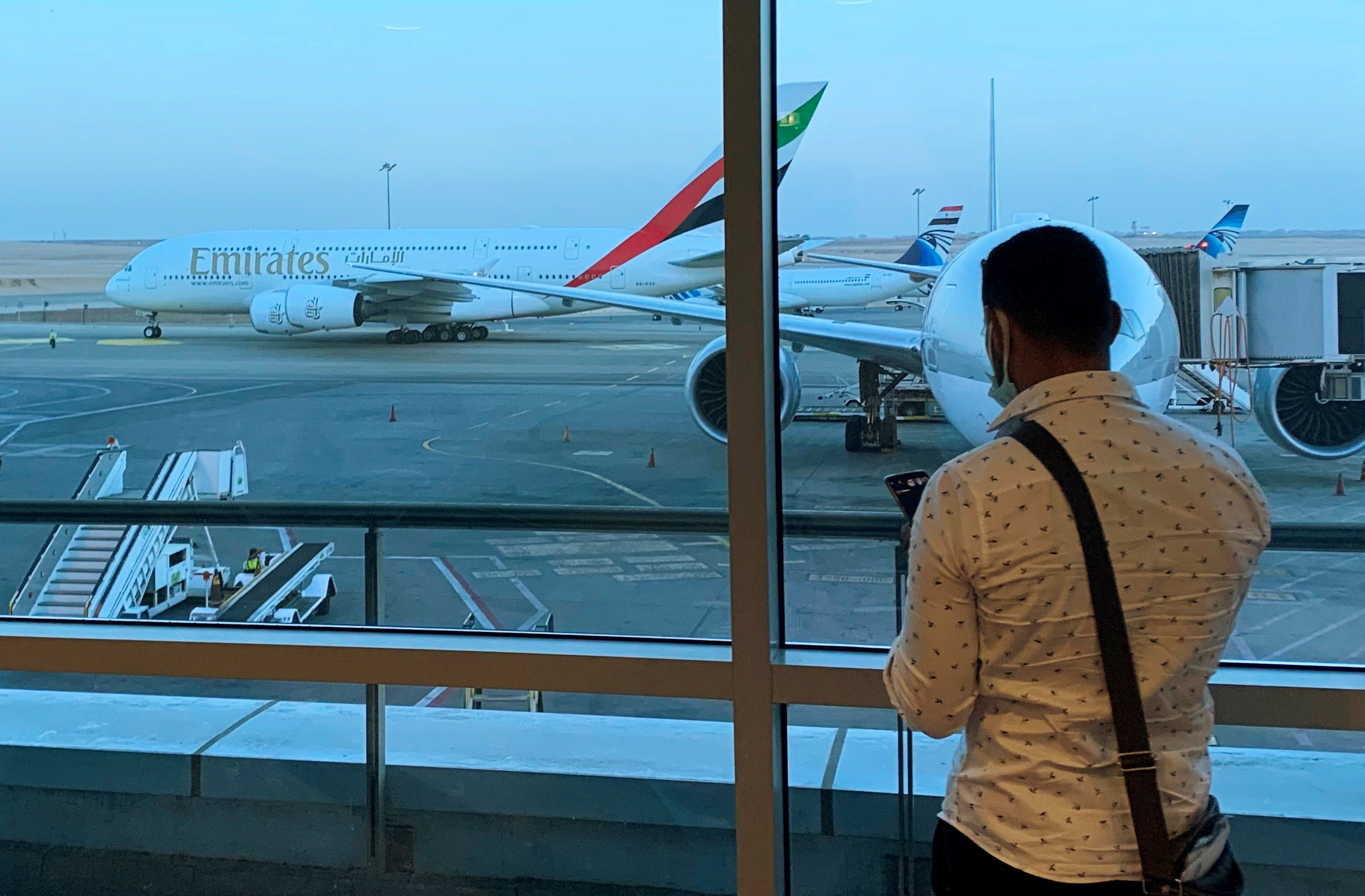 A passenger waits for his Emirates Airlines' flight departure to Dubai at Cairo's International Airport, Egypt July 20, 2021. REUTERS/Amr Abdallah Dalsh