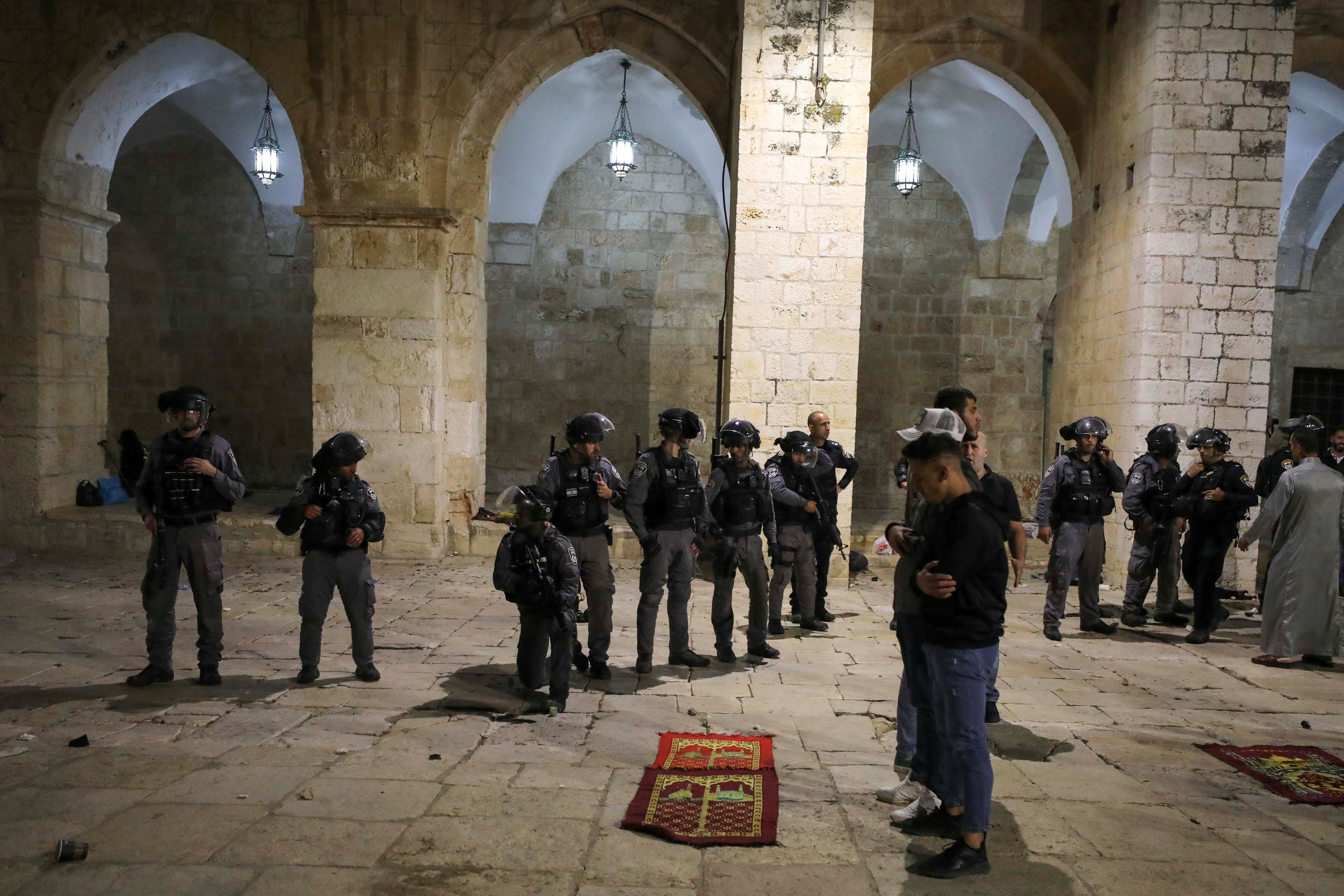 Palestinians pray as Israeli police gather during clashes at the compound that houses Al-Aqsa Mosque, known to Muslims as Noble Sanctuary and to Jews as Temple Mount, amid tension over the possible eviction of several Palestinian families from homes on land claimed by Jewish settlers in the Sheikh Jarrah neighbourhood, in Jerusalem's Old City, May 7, 2021. REUTERS/Ammar Awad