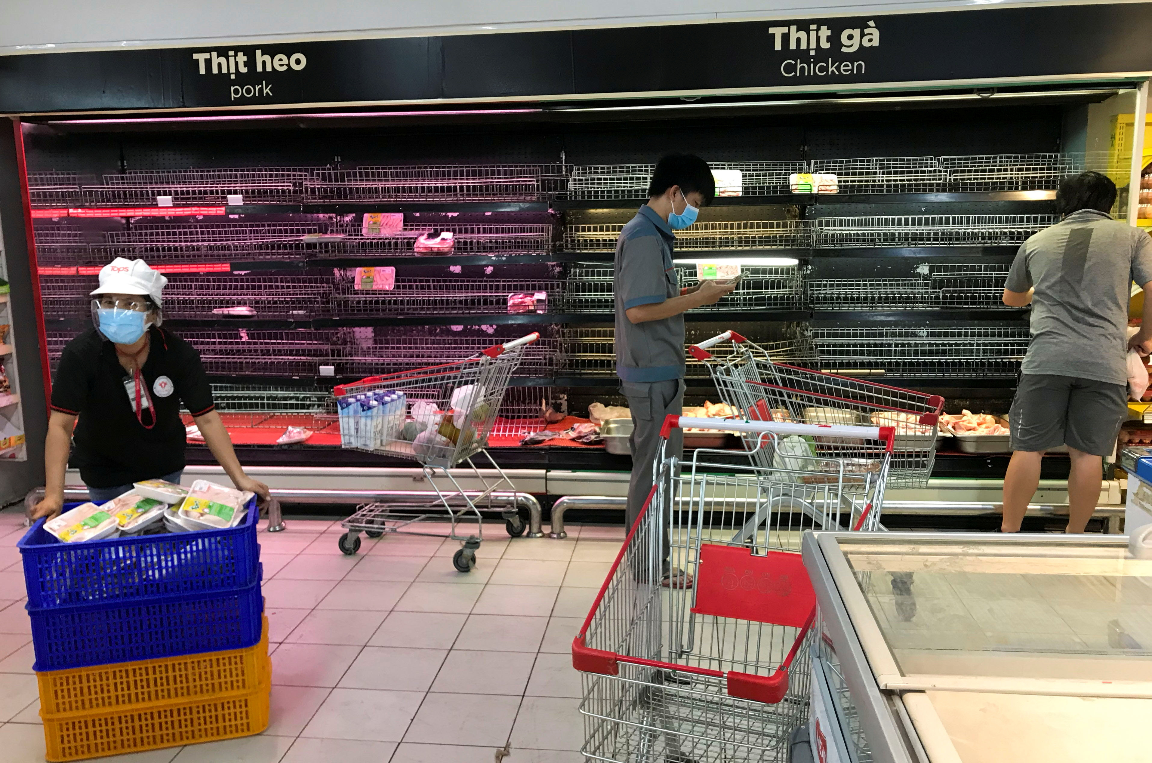 Customers search for food on near empty shelves that were depleted due to panic buying amid the coronavirus disease (COVID-19) pandemic in Ho Chi Minh City, Vietnam August 21, 2021. REUTERS/Stringer
