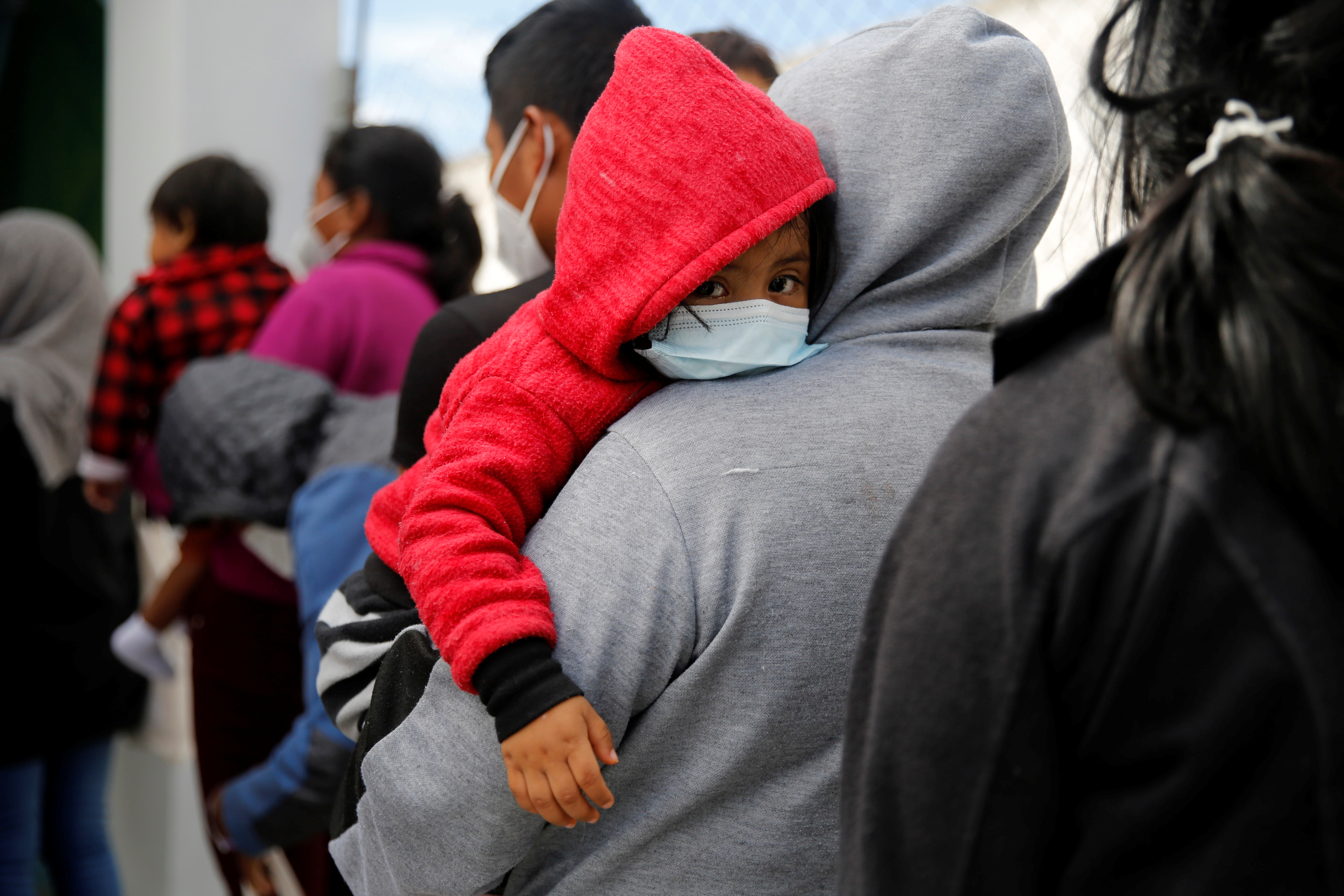 Families queue at a migration facility after being deported from the U.S. under Title 42 as part of the efforts of the U.S. government to expedite removals of some families to dissuade record numbers of migrants from making the journey north, at the La Aurora International airport in Guatemala City, Guatemala August 4, 2021. REUTERS/Luis Echeverria