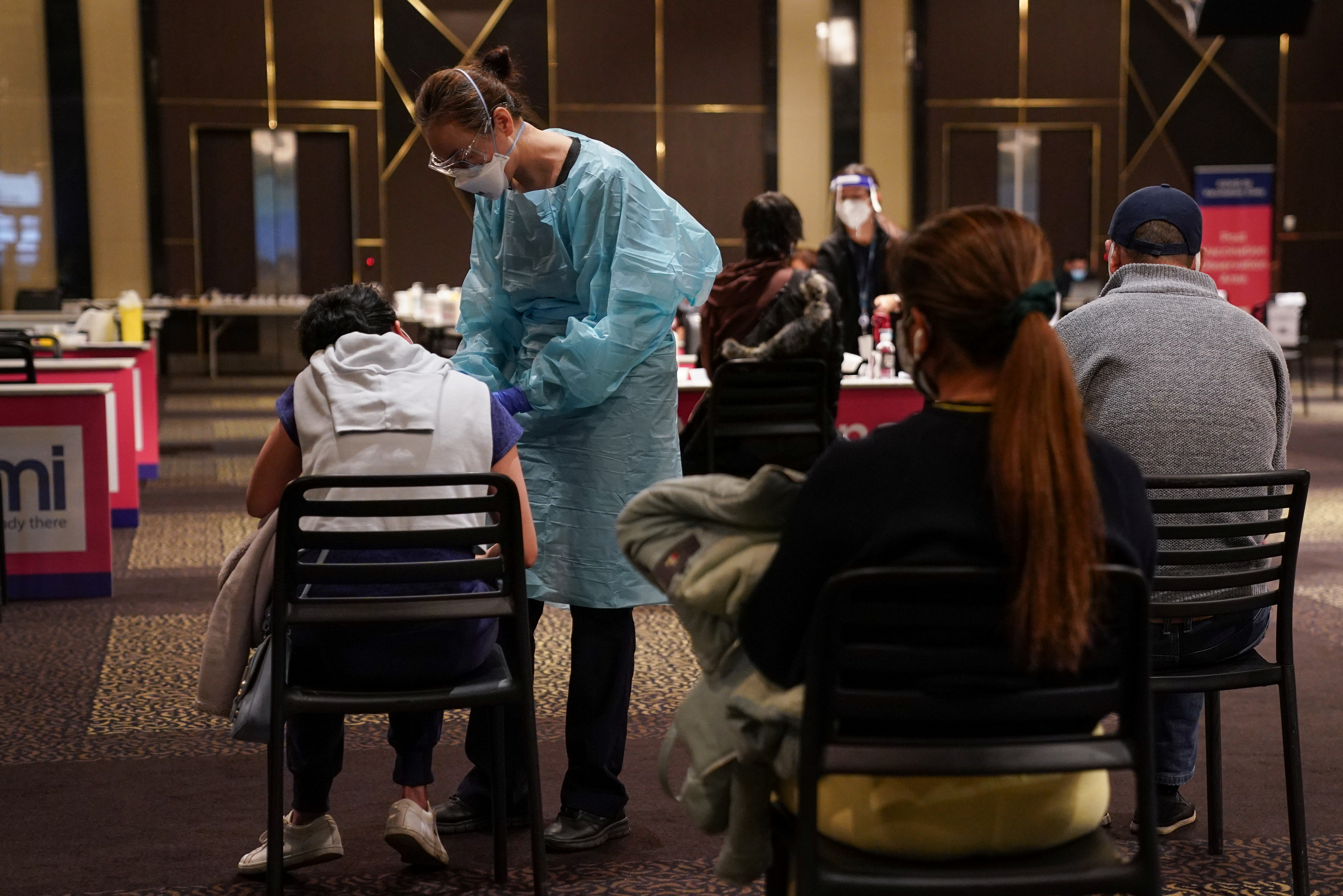 A medical staff worker speaks with a patient about to receive the AstraZeneca vaccine at a coronavirus disease (COVID-19) vaccination clinic at the Bankstown Sports Club during a lockdown to curb an outbreak of cases in Sydney, Australia, August 25, 2021.  REUTERS/Loren Elliott