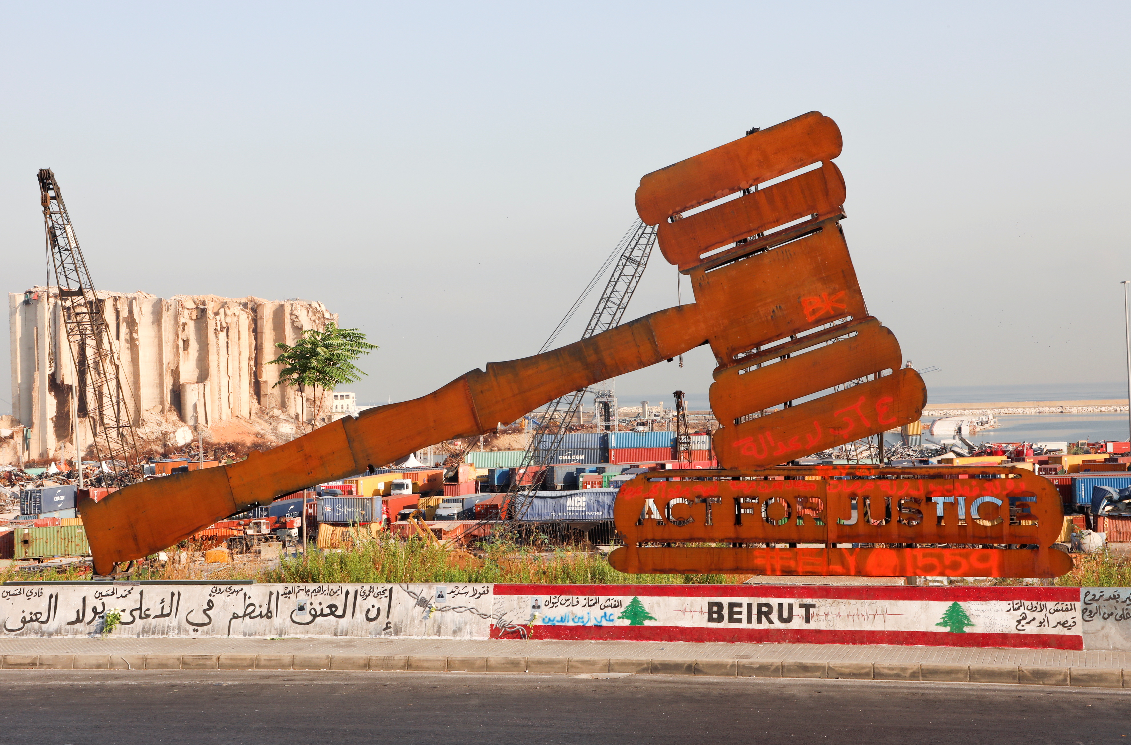 A justice symbol monument is seen near the grain silo damaged during last year's Beirut port blast as Lebanon marks the one-year anniversary of Beirut port explosion, in Beirut, Lebanon August 4, 2021. REUTERS/Mohamed Azakir