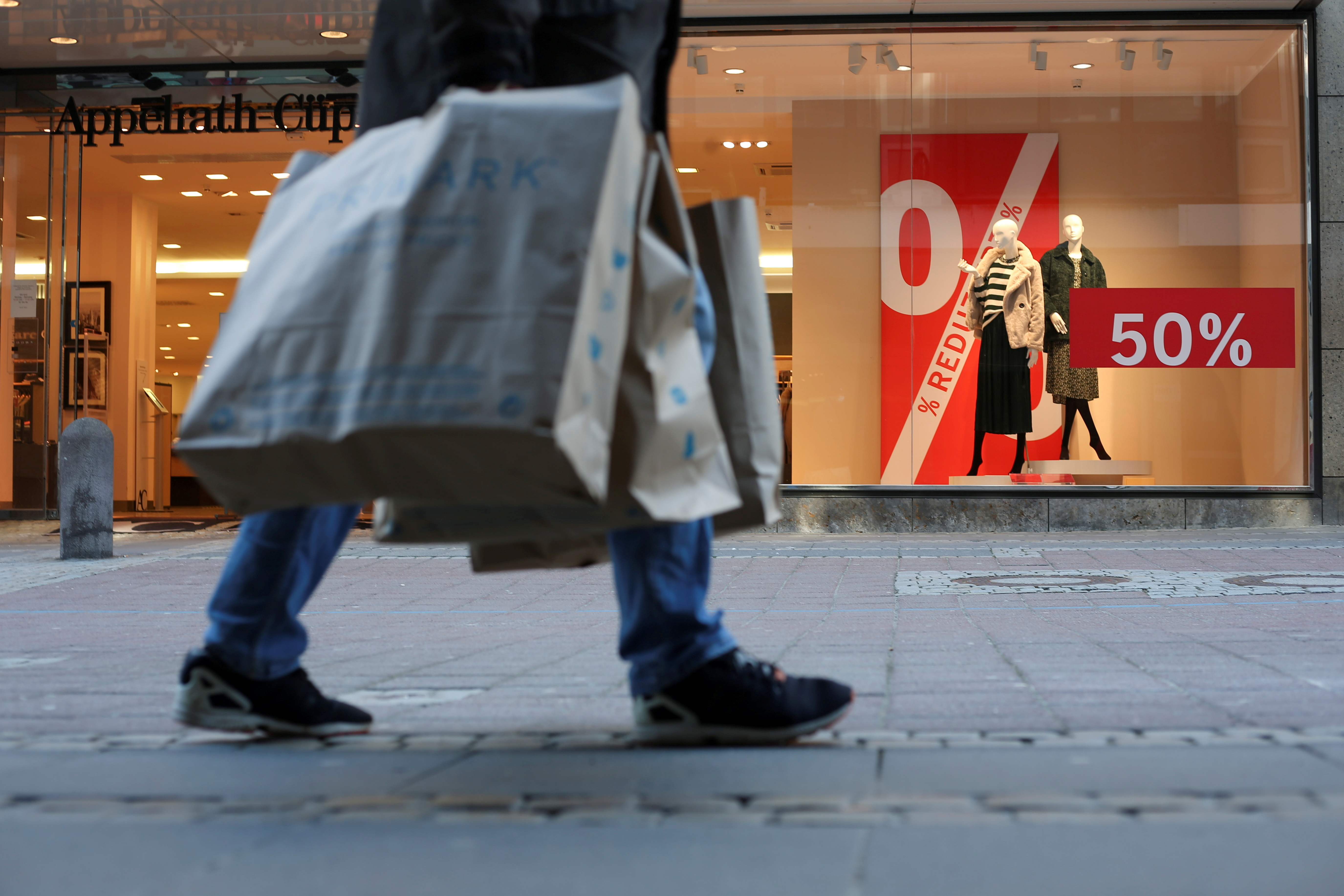 A person holding shopping bags walks past a store as the coronavirus disease (COVID-19) lockdown measures are eased in Kiel, Germany, March 9, 2021. REUTERS/Cathrin Mueller/File Photo