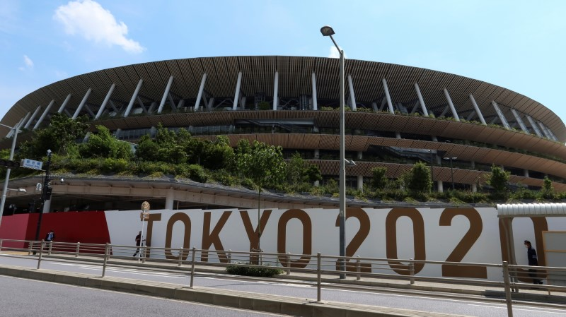 People walk outside the security fence of Olympic Stadium (National Stadium) built for Tokyo Olympic Games, that have been postponed to 2021 due to the coronavirus disease (COVID-19) outbreak, in Tokyo, Japan June 11, 2021. REUTERS/Pawel Kopczynski