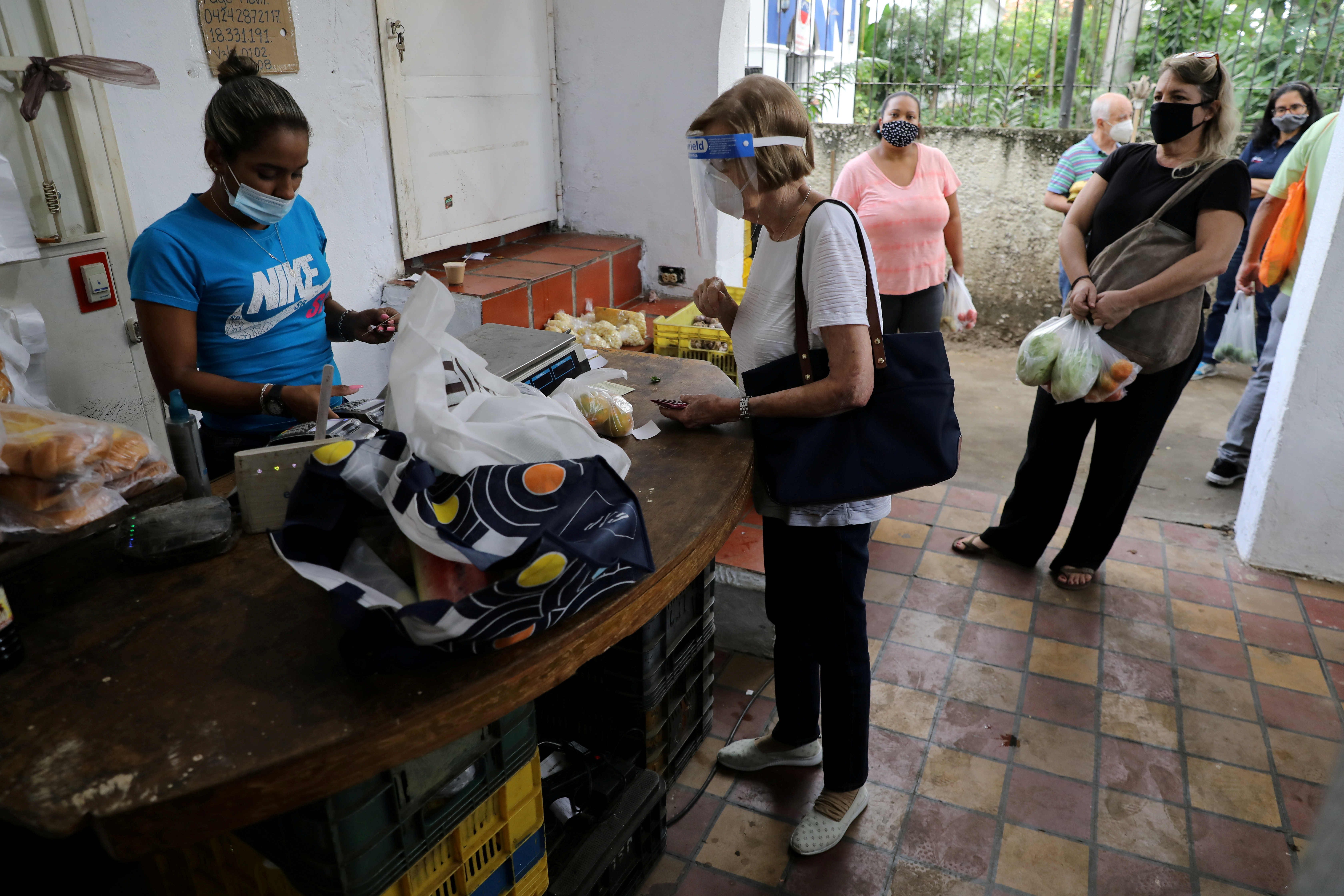 People wearing protective masks due to the coronavirus pandemic queue in an open-air fruit and vegetable market in Caracas, Venezuela December 22, 2020. Picture taken December 22, 2020. REUTERS/Manaure Quintero/File Photo