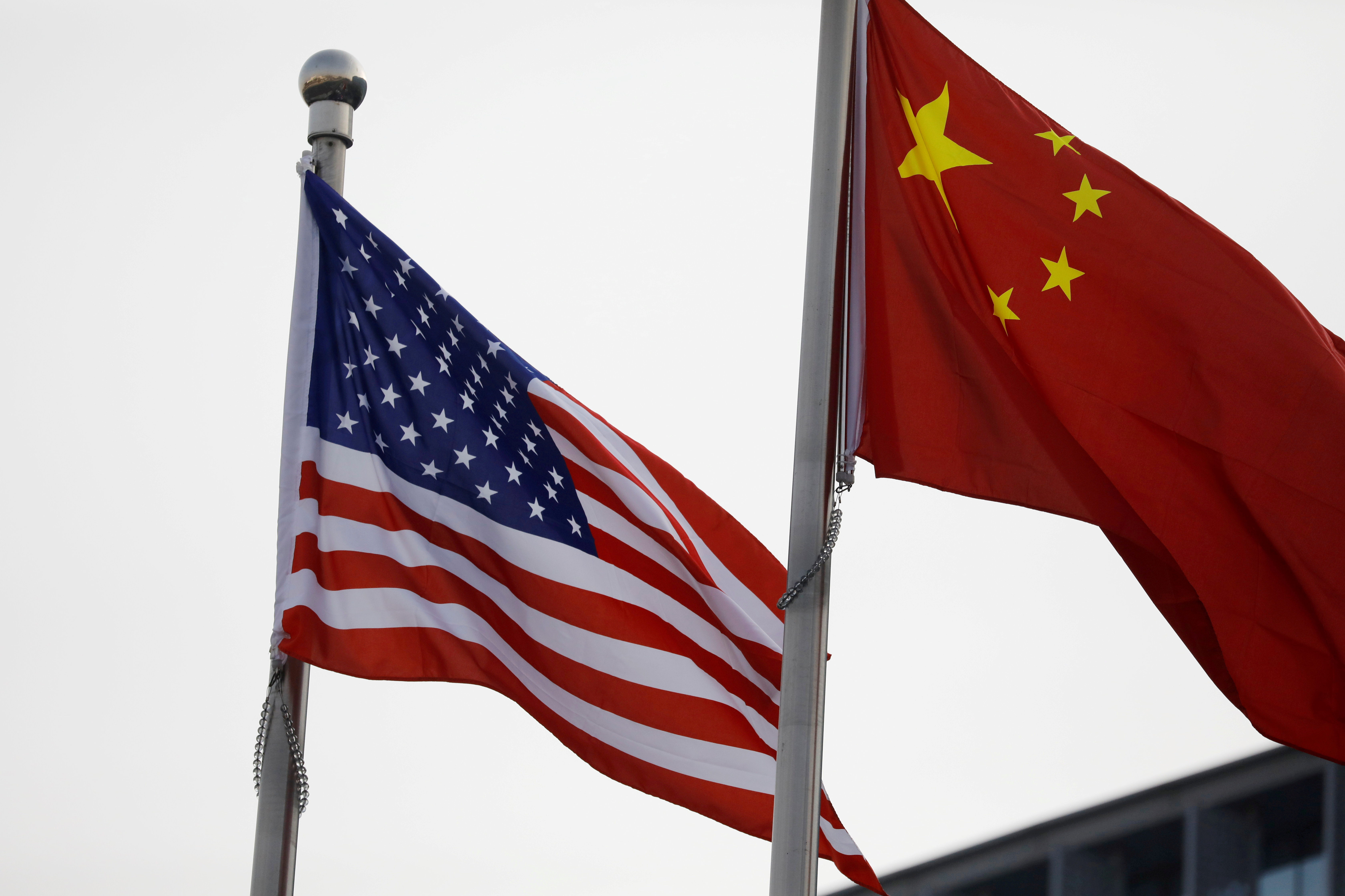 Chinese and U.S. flags flutter outside the building of an American company in Beijing, China January 21, 2021. REUTERS/Tingshu Wang
