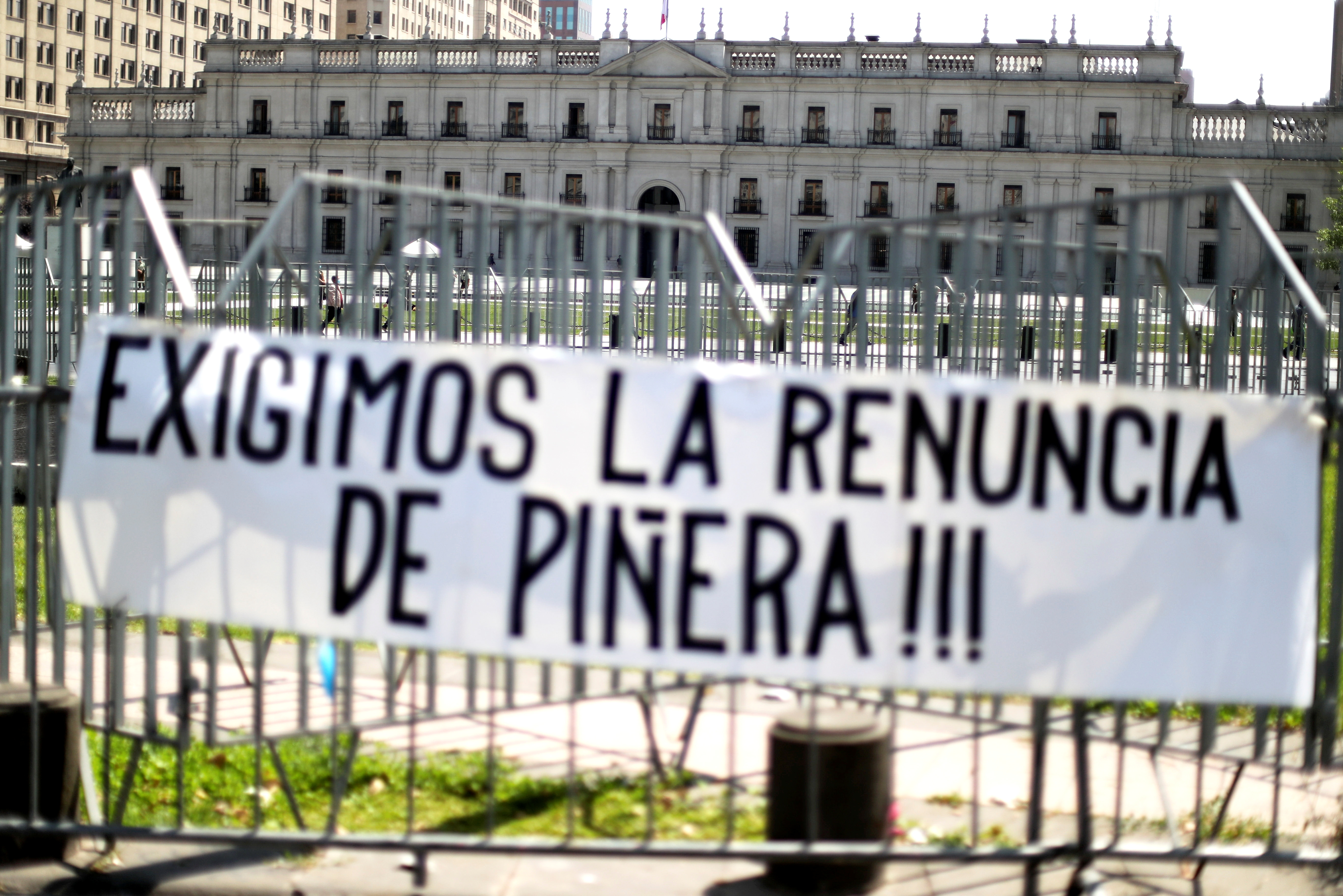 A banner hangs on a fence in front of the government house reading ''We demand the resignation of Pinera'' during a rally calling for the cancellation of a presidential veto of a bill that would improve the working conditions of Chilean teachers, and to request the Chilean President Sebastian Pinera's resignation, in Santiago, Chile, October 13, 2021. REUTERS/Ivan Alvarado