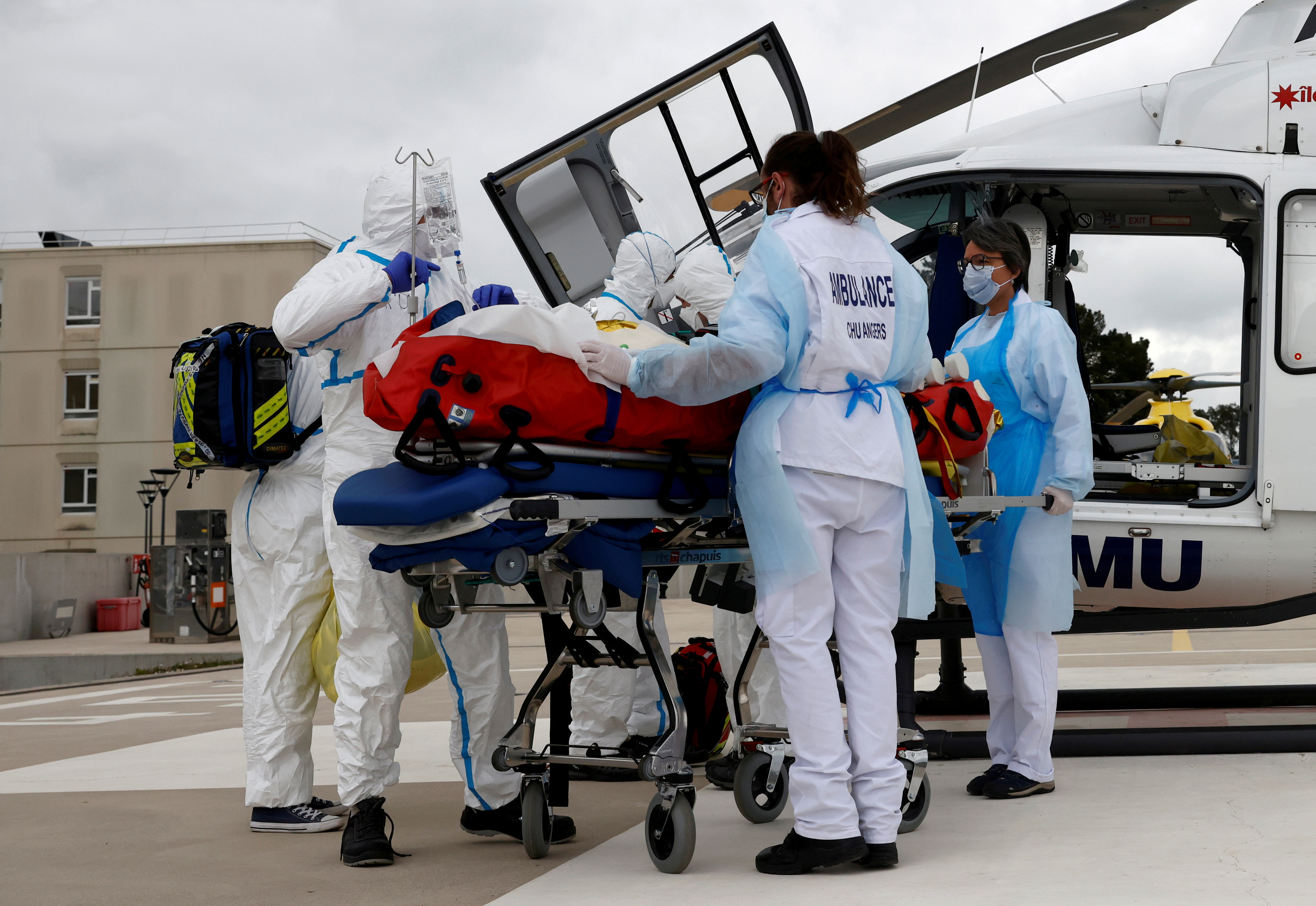 A medical crew from Angers hospital prepares to take away a COVID-19 patient on a stretcher after his transfer by helicopter from the Ile de France region to Angers hospital, France, March 15, 2021. REUTERS/Stephane Mahe/File Photo