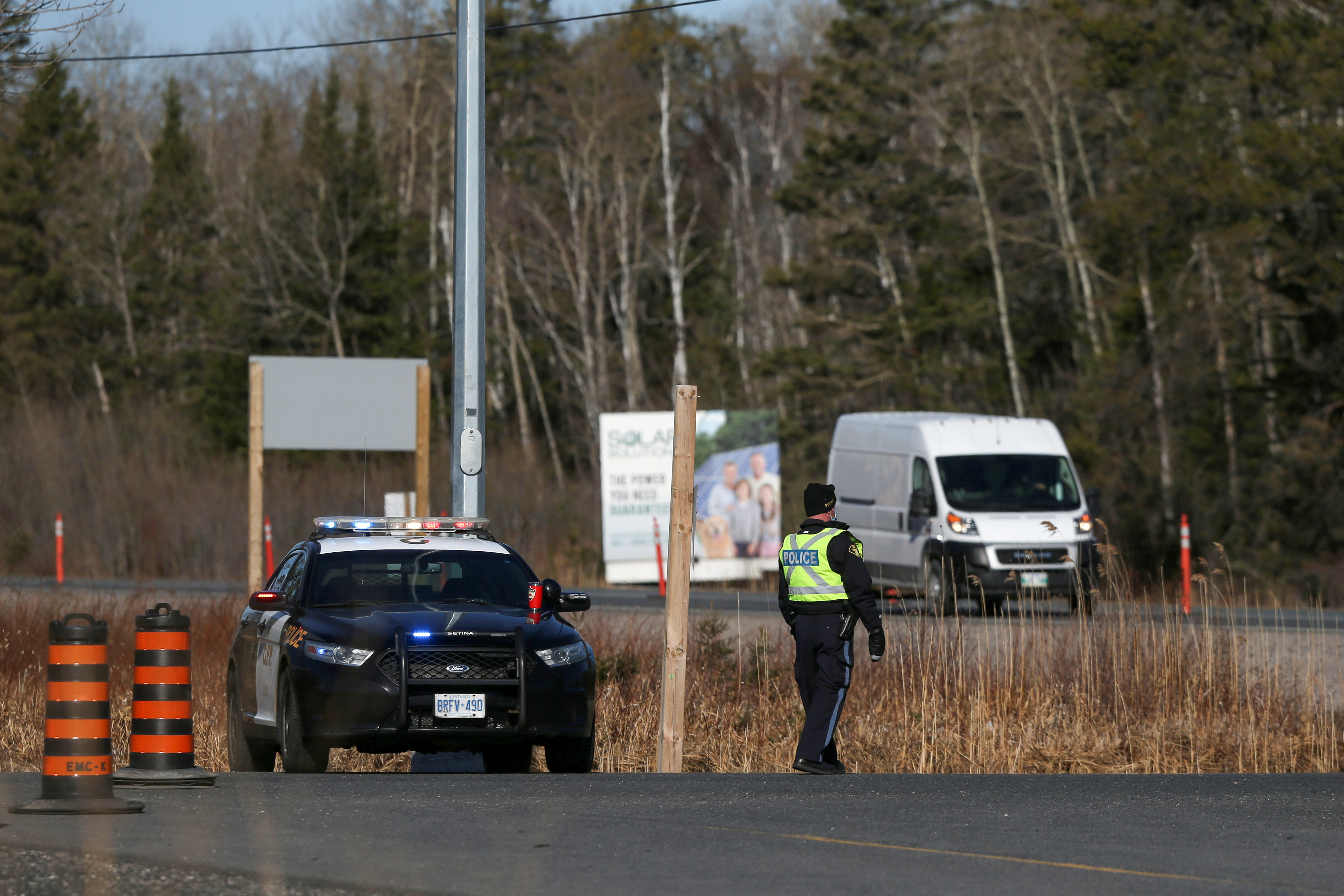 A police officer prepares to stop motorists at a checkpoint at the Manitoba-Ontario provincial boundary after new coronavirus disease (COVID-19) restrictions came into effect, limiting non-essential travel into the province of Ontario, near Whiteshell, Manitoba, Canada April 19, 2021.  REUTERS/Shannon VanRaes