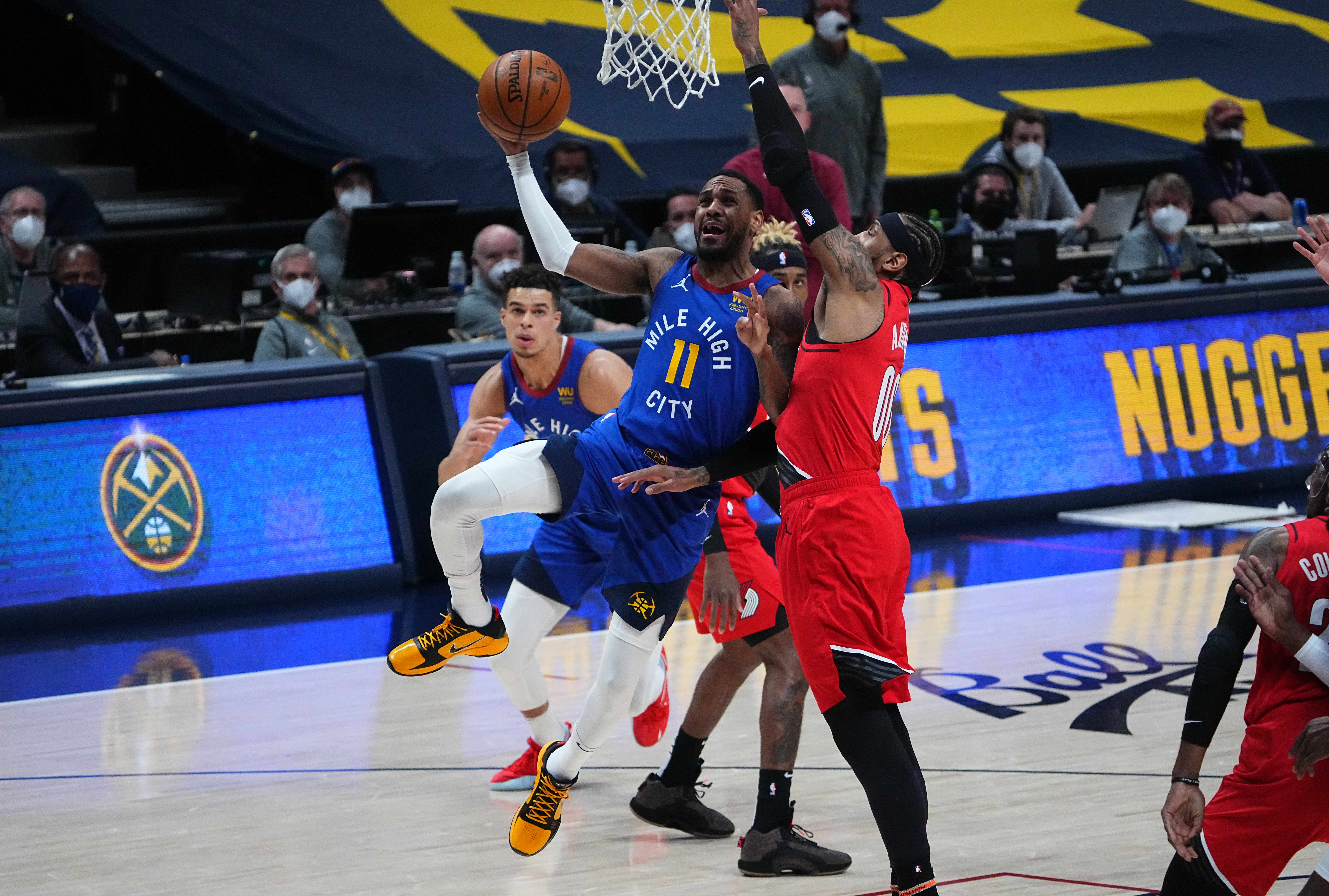 Jun 1, 2021; Denver, Colorado, USA; Denver Nuggets guard Monte Morris (11) shoots the ball past Portland Trail Blazers forward Carmelo Anthony (00) in the second quarter during game five in the first round of the 2021 NBA Playoffs. at Ball Arena. Mandatory Credit: Ron Chenoy-USA TODAY Sports