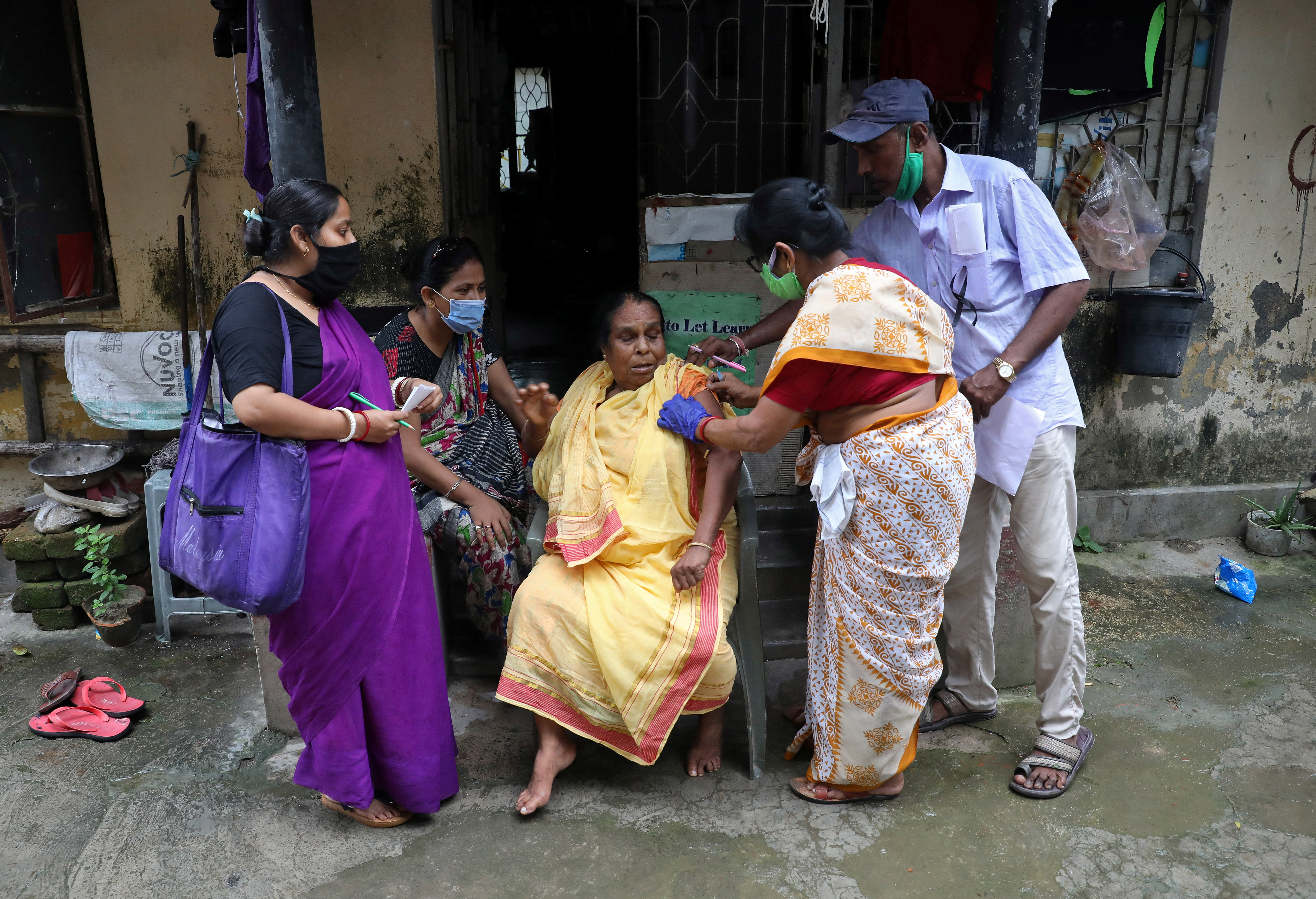 Rekha Ghosh, 64, reacts a she receives a dose of COVISHIELD, a coronavirus disease vaccine manufactured by Serum Institute of India, outside her house during a door-to-door vaccination drive in Kolkata, India, August 12, 2021. REUTERS/Rupak De Chowdhuri