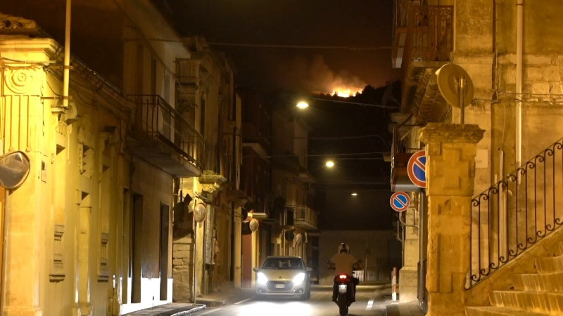 A wildfire burns a pine forest on the hills seen from Giarratana village, on the island of Sicily, Italy August 11, 2021 in a screengrab taken from video. Content shot August 11, 2021. REUTERS/Antonio Parrinello