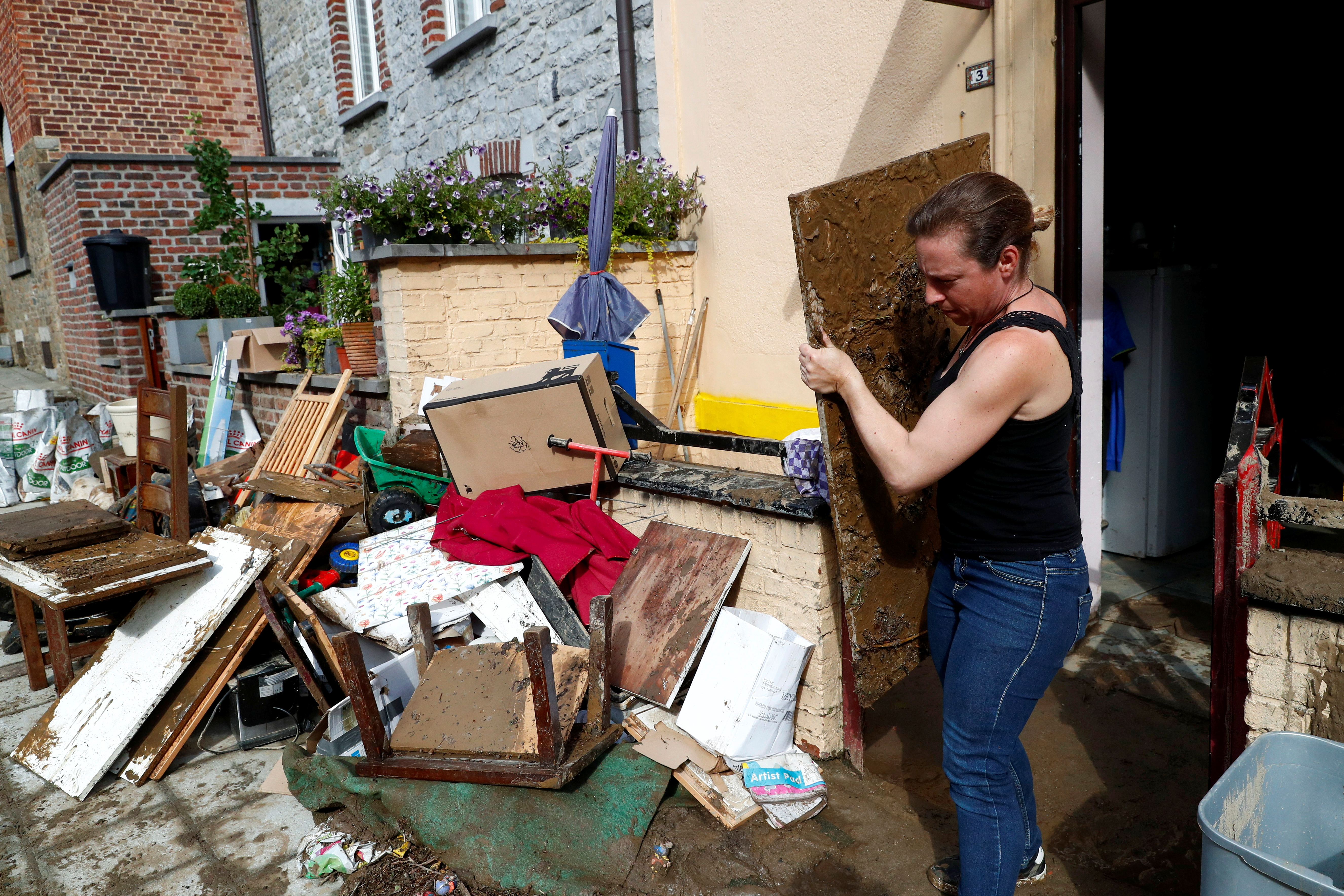 Mulher trabalha para recuperar seus pertences após fortes chuvas em Dinant, Bélgica, 25 de julho de 2021. REUTERS / Johanna Geron