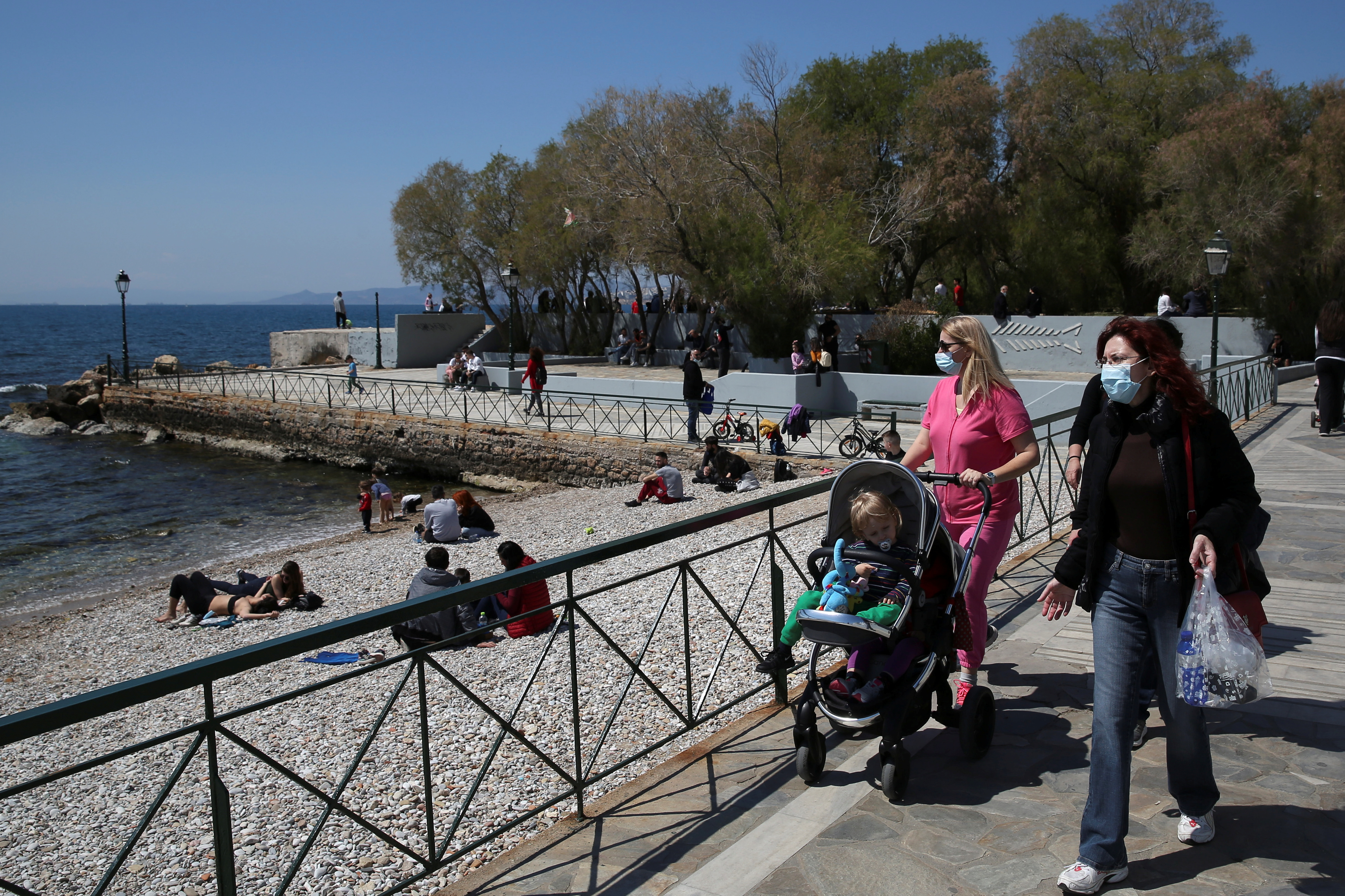 People walk near the beach following the easing of measures against the spread of the coronavirus disease (COVID-19) in Faliro suburb, near Athens, Greece, April 3, 2021. REUTERS/Costas Baltas