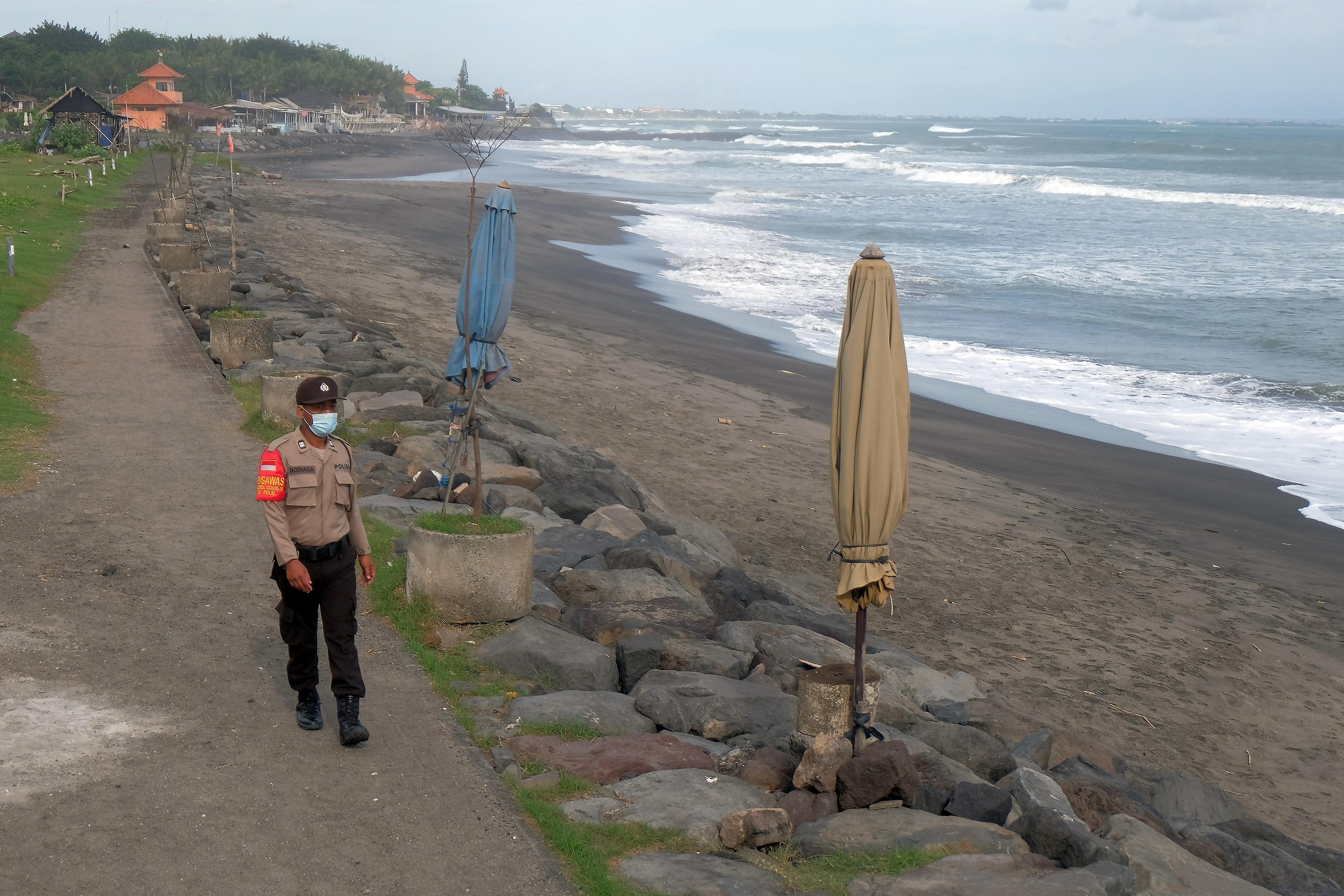 A police officer patrols at an empty beach amid the coronavirus disease (COVID-19) outbreak, in Badung, Bali, Indonesia, July 17, 2021, in this photo taken by Antara Foto. Antara Foto/Nyoman Hendra Wibowo/ via REUTERS