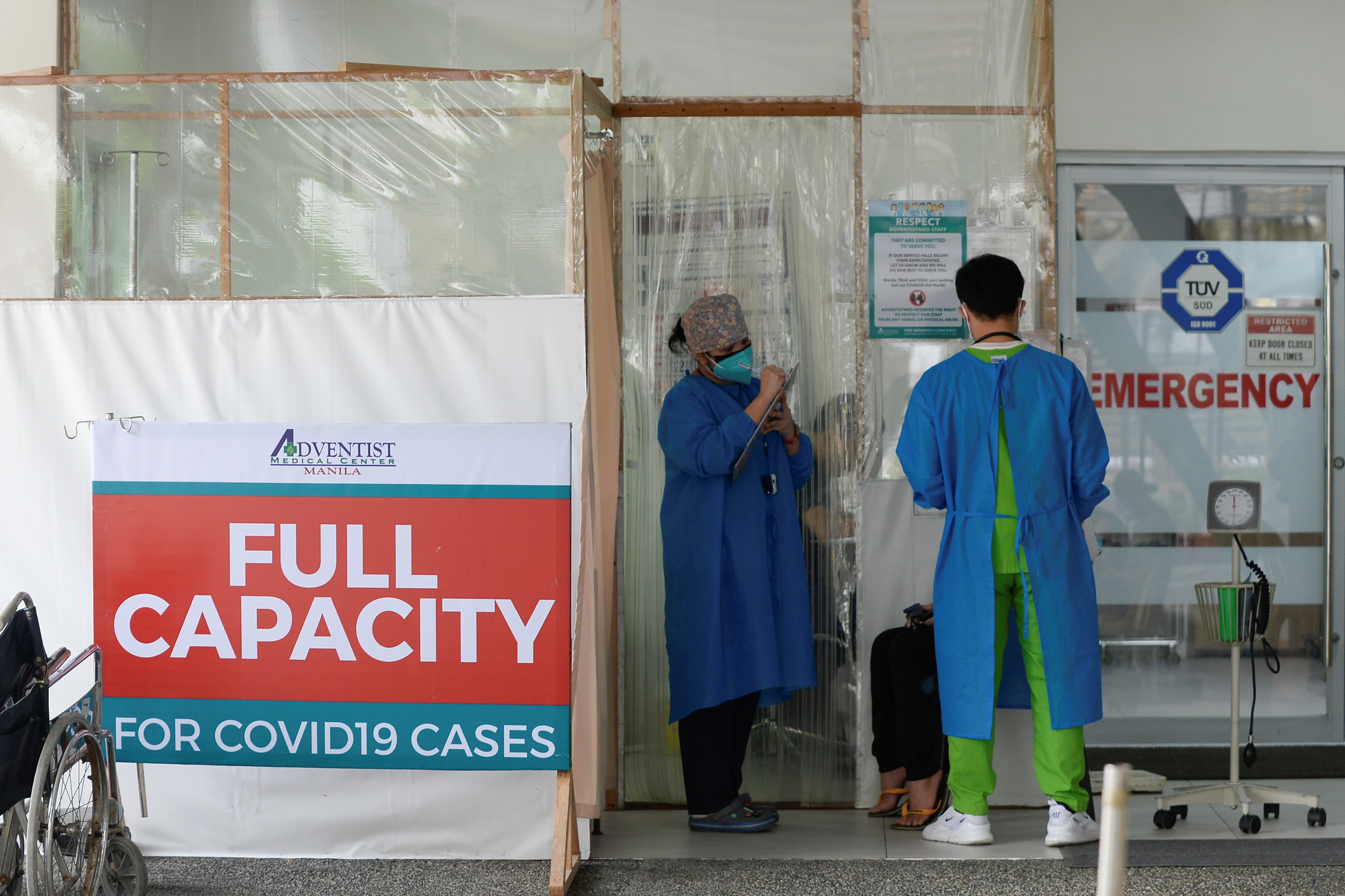Health workers assess a patient outside the emergency room at the Adventist Medical Center, where a sign indicating that the hospital's coronavirus disease (COVID-19) facility is at full capacity is displayed, in Pasay, Philippines, April 9, 2021. REUTERS/Lisa Marie David