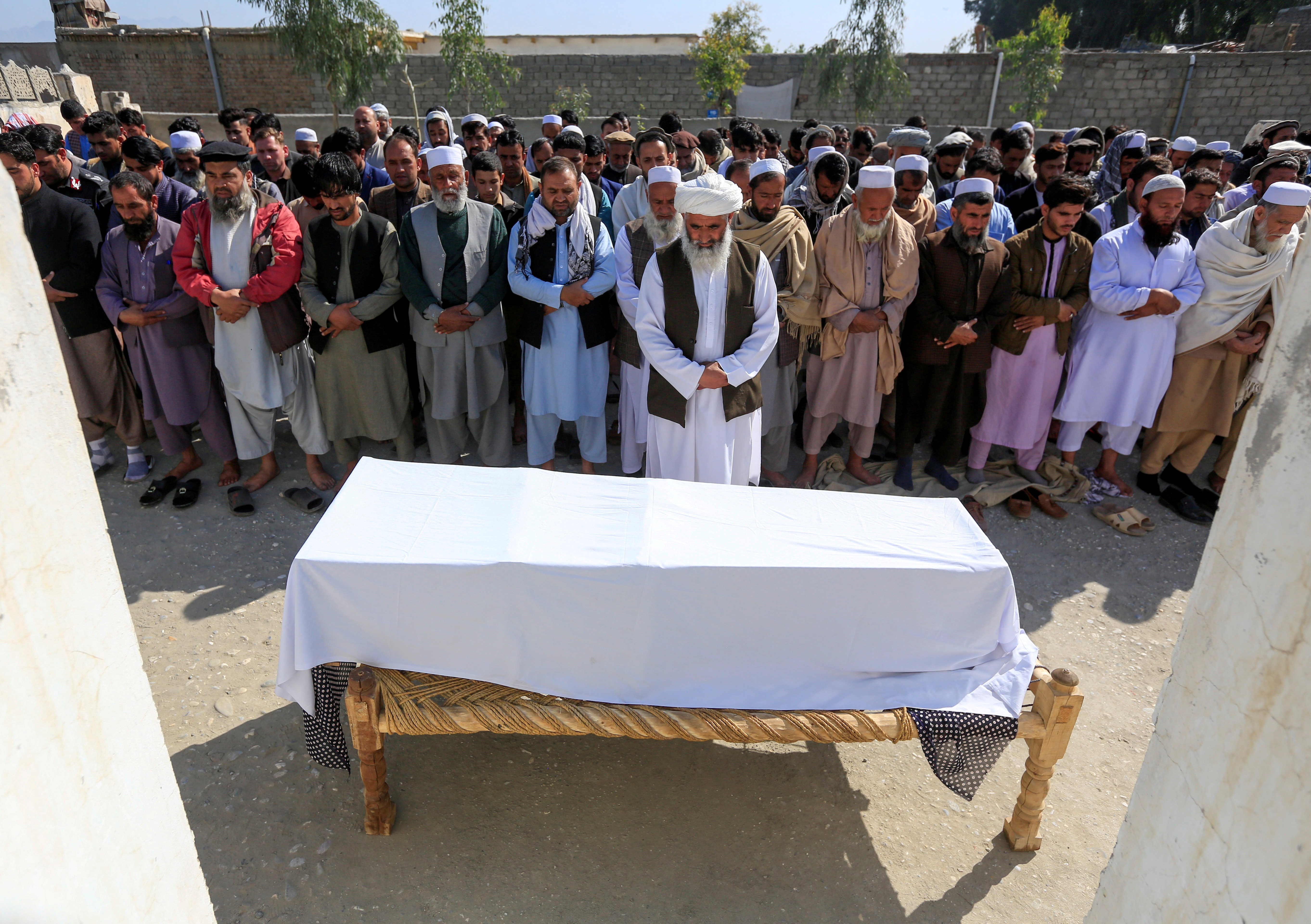 Afghan men pray in front of the coffin of one of three female media workers who were shot and killed by unknown gunmen, in Jalalabad, Afghanistan March 3, 2021. REUTERS/Parwiz/