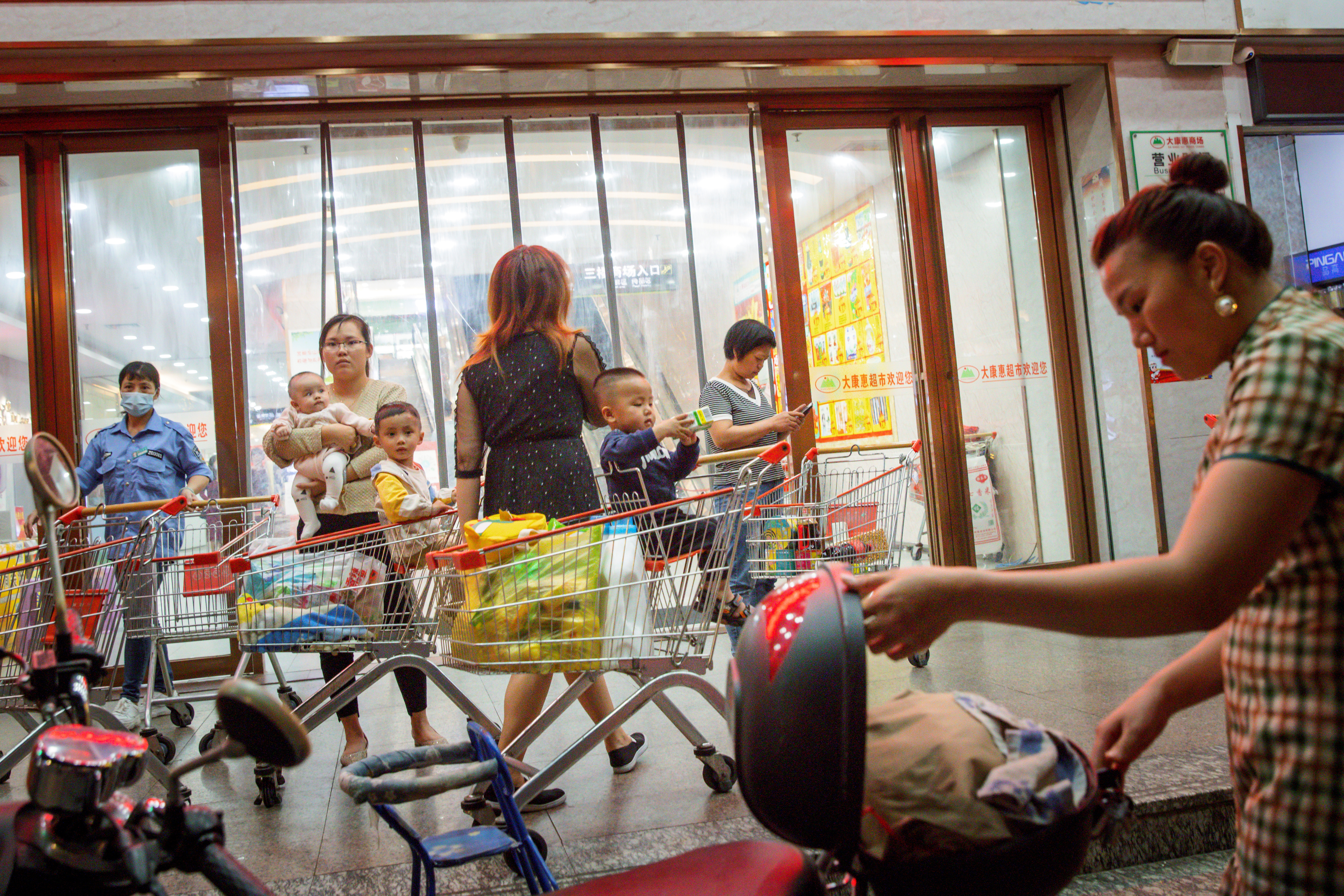 A woman holds a baby outside a supermarket in Qinzhou, Guangxi province, China, April 12, 2021. Picture taken April 12, 2021.  REUTERS/Thomas Peter