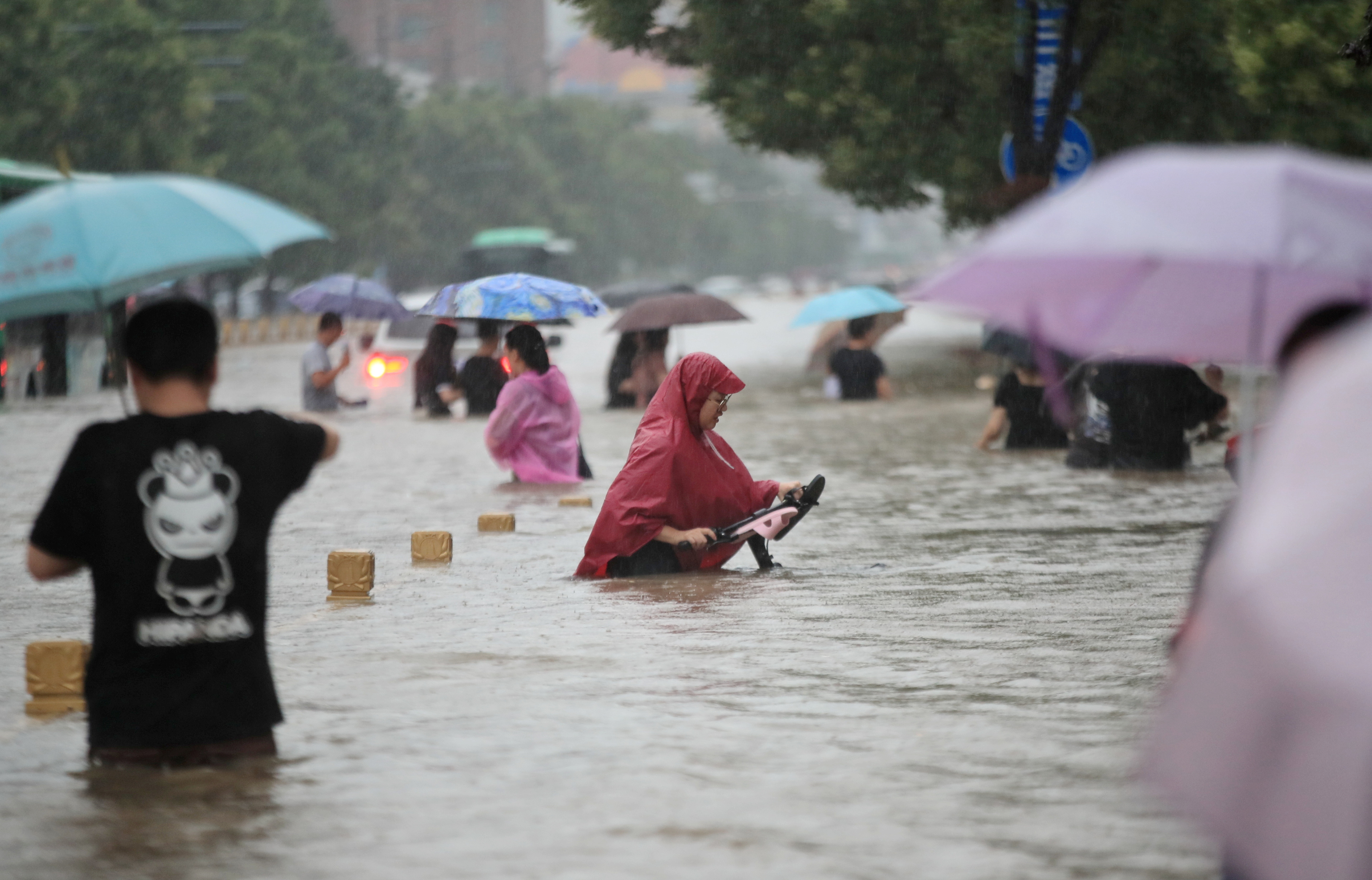 Residents wade through floodwaters on a flooded road amid heavy rainfall in Zhengzhou, Henan province, China July 20, 2021. China Daily via REUTERS