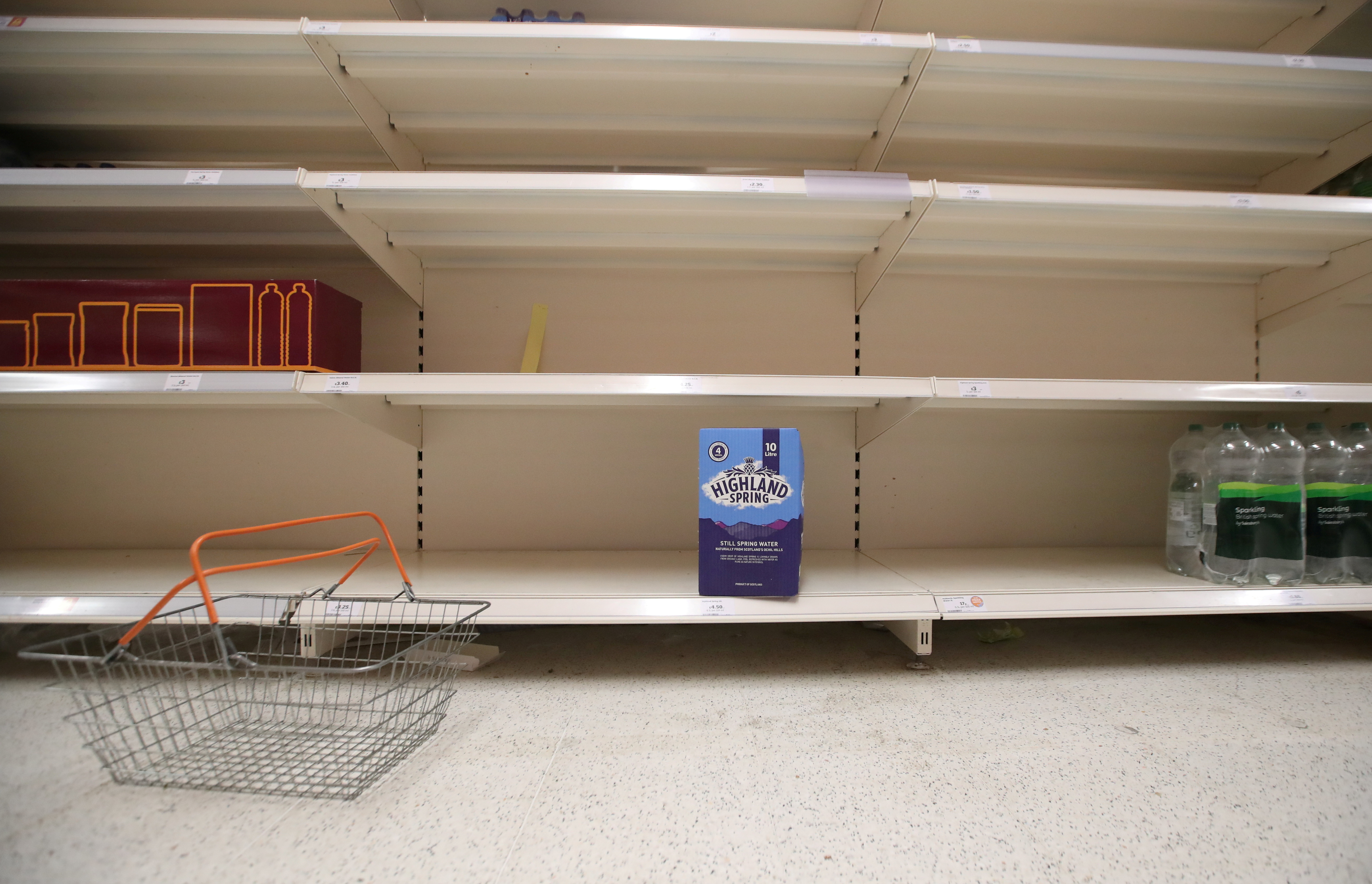 A shopping basket is discarded next to empty shelves of the soft drinks aisle, in Sainsbury's supermarket in Harpenden, Britain, September 22, 2021.  REUTERS/Peter Cziborra