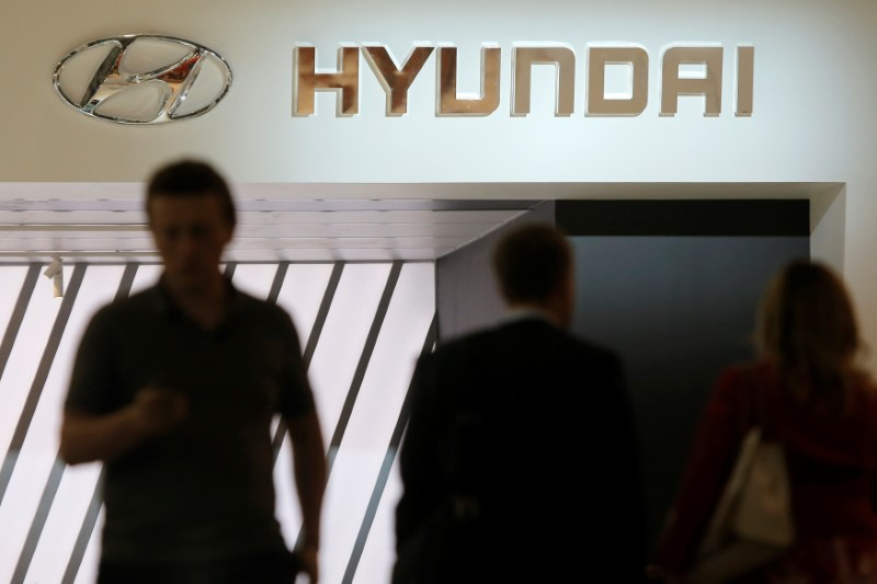 People walk past the logo of Hyundai on the car maker's booth at the 2016 Moscow International Auto Salon in Moscow, Russia, August 24, 2016. REUTERS/Maxim Shemetov
