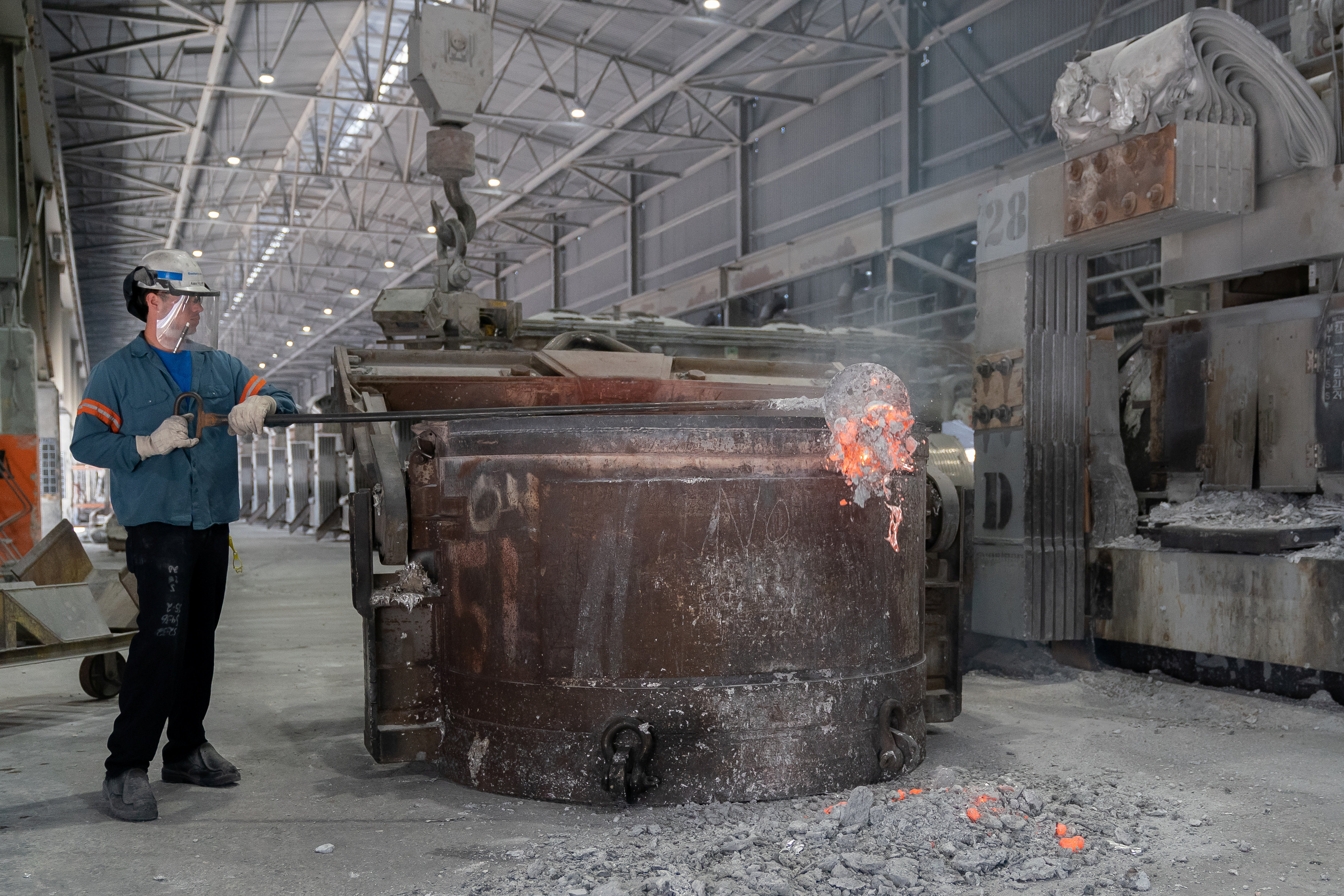 A metal worker clears a slag off the top of molten aluminum in a siphoning crucible at Century Aluminum Company in  Hawesville, Kentucky, U.S. May 14, 2019. Picture taken May 14, 2019.  REUTERS/Bryan Woolston
