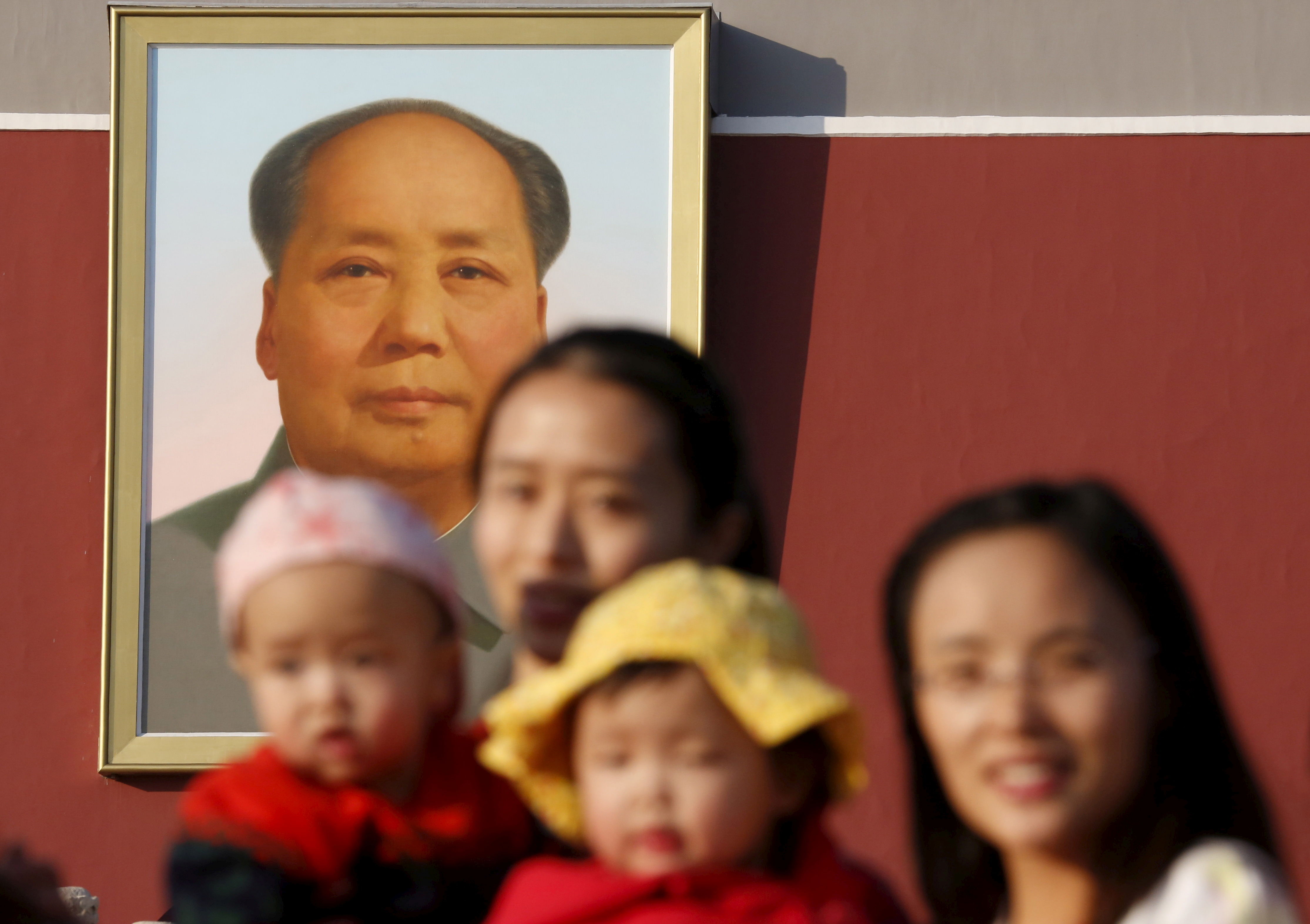 Two women and their babies pose for photographs in front of the giant portrait of late Chinese chairman Mao Zedong on the Tiananmen Gate in Beijing November 2, 2015.  REUTERS/Kim Kyung-Hoon/File Photo - RC2MHN9SUGBY