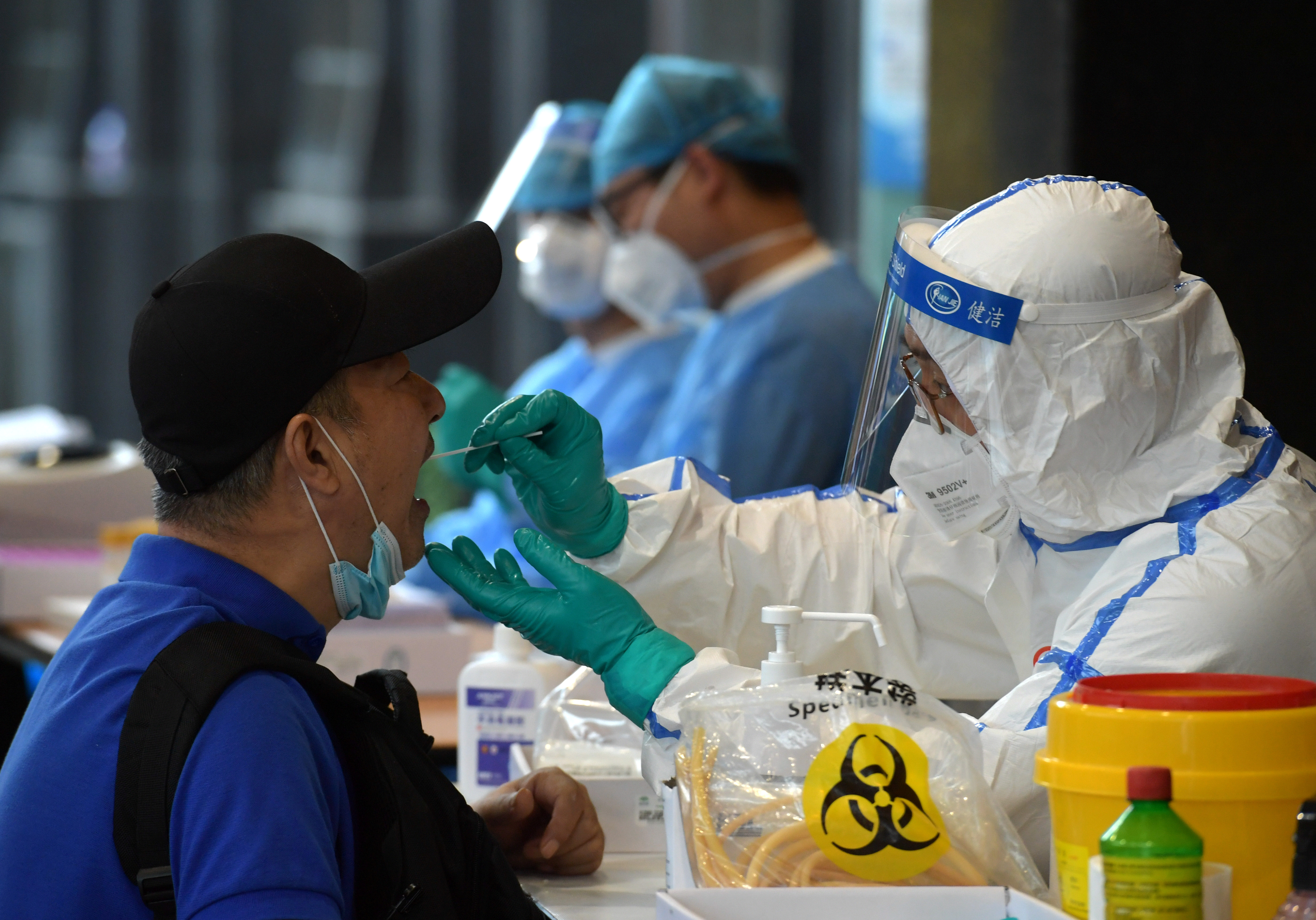A medical staff in protective suit collects swabs from people who have recently travelled to Beijing for nucleic acid tests, following new cases of coronavirus disease (COVID-19) infections at the Chinese capital, in Nanjing, Jiangsu province, China June 15, 2020. China Daily via REUTERS/Files