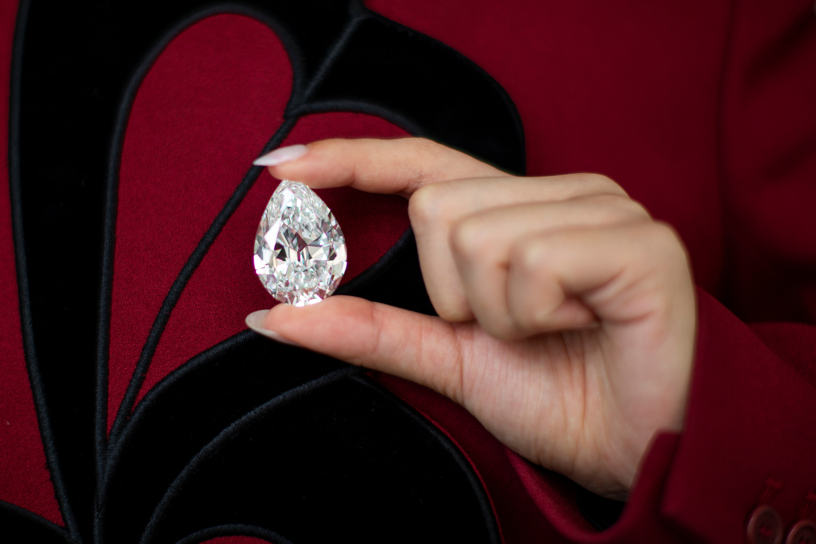An employee of Sotheby's poses with a rare pear-Shaped D Colour Flawless 100+ carat diamond at Sotheby's in New York City, New York, U.S., June 21, 2021. REUTERS/Eduardo Munoz