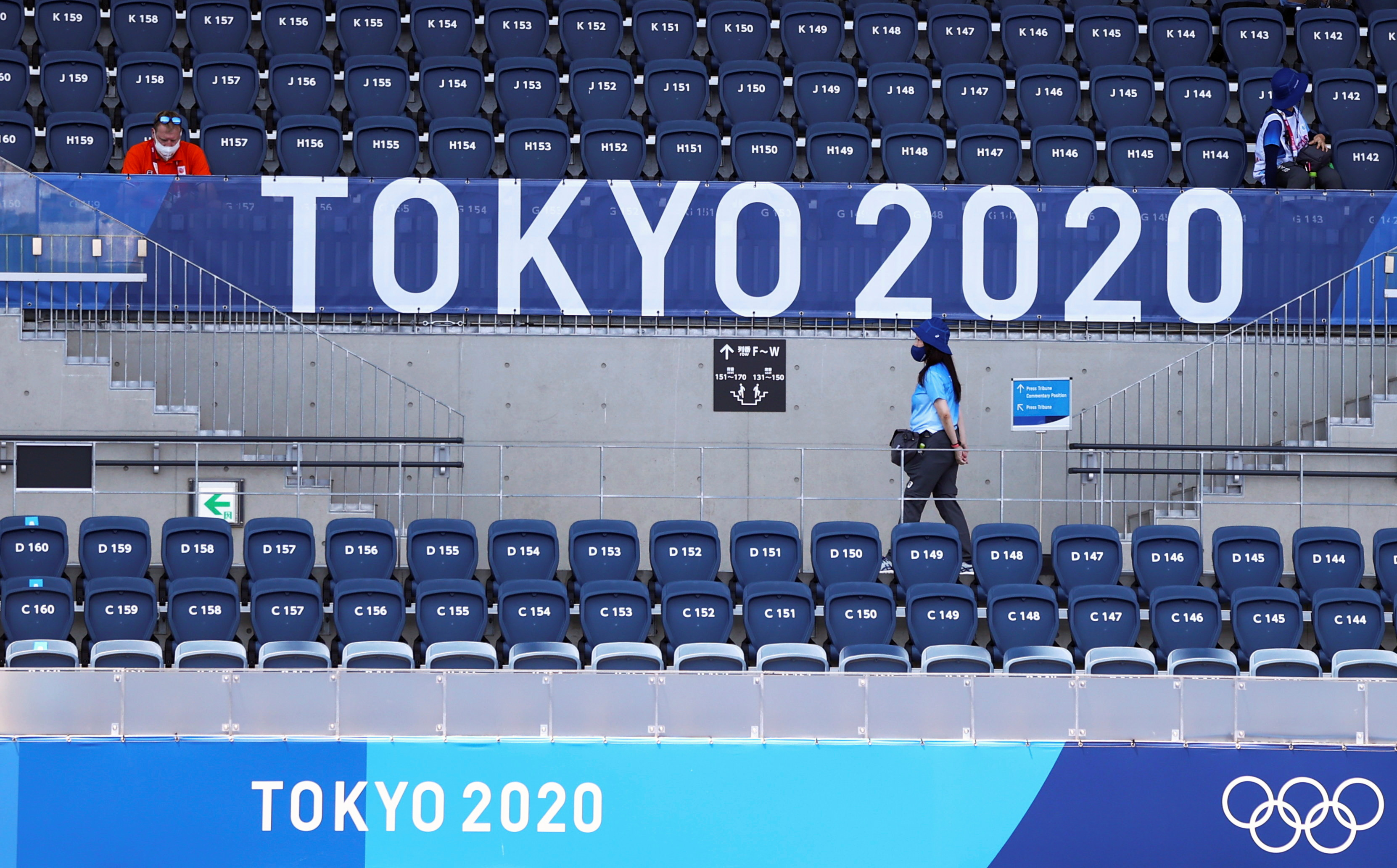 A spectator sits as a volunteer walks beaneath a logo during the Tokyo 2020 Olympic Games in at the Oi Hockey Stadium in Tokyo, Japan, July 24, 2021. REUTERS/Siphiwe Sibeko