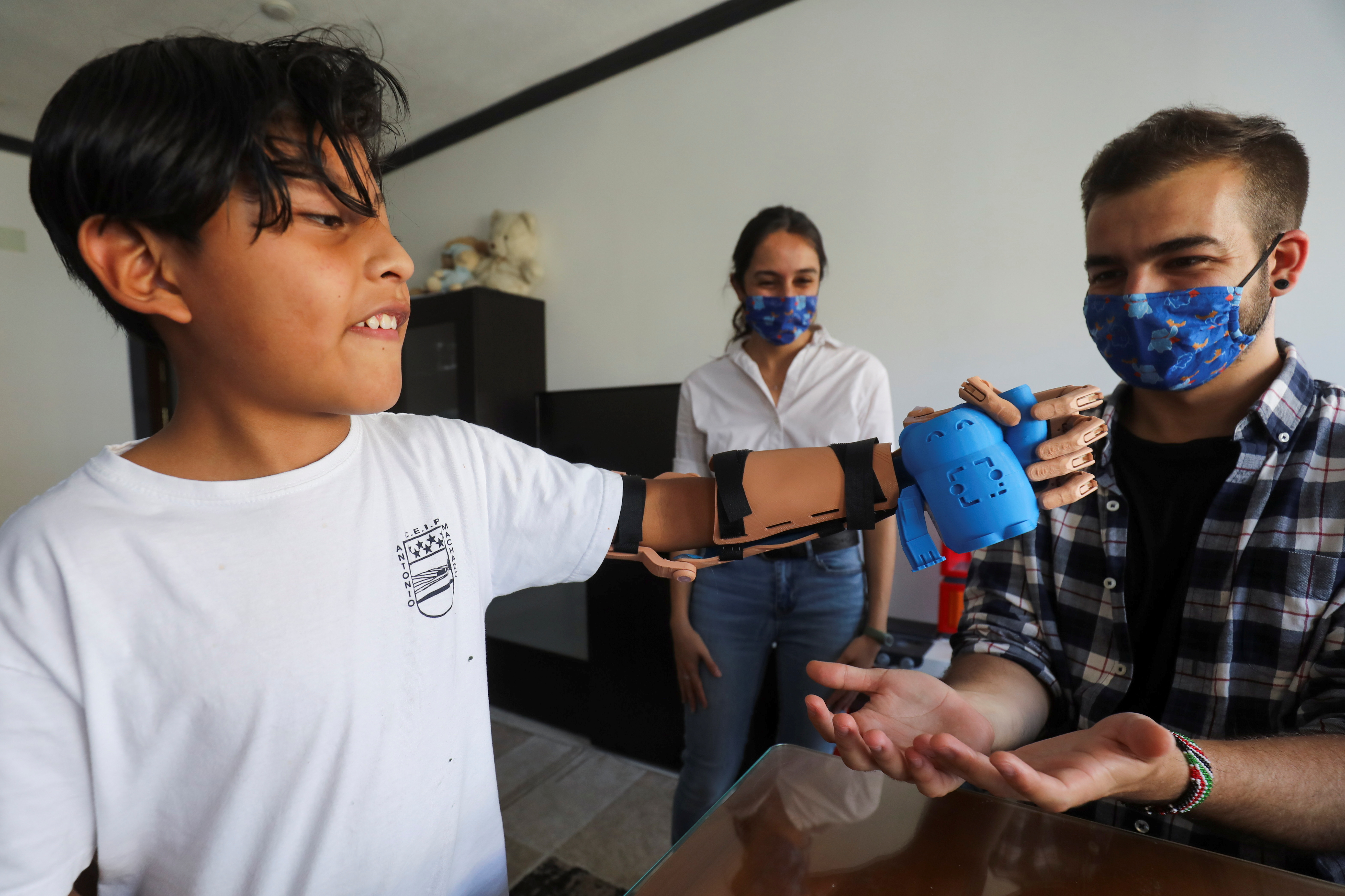 Juan Moyolema, an 8-year-old boy who was born missing the lower part of his left arm, picks a toy up with a 3D printed tailor-made prosthetic beside Guillermo Martinez, founder of Madrid-base social entity Ayudame3D, at their home in Parla, near Madrid, Spain, May 18, 2021. Picture taken May 18, 2021. REUTERS/Sergio Perez