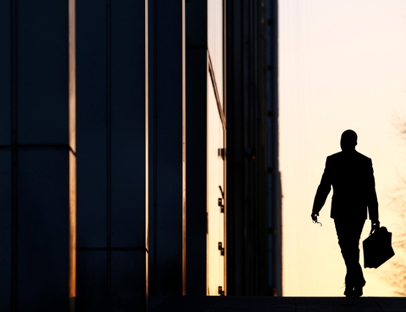 A worker arrives at his office in the Canary Wharf business district in London February 26, 2014. REUTERS/Eddie Keogh/File Photo