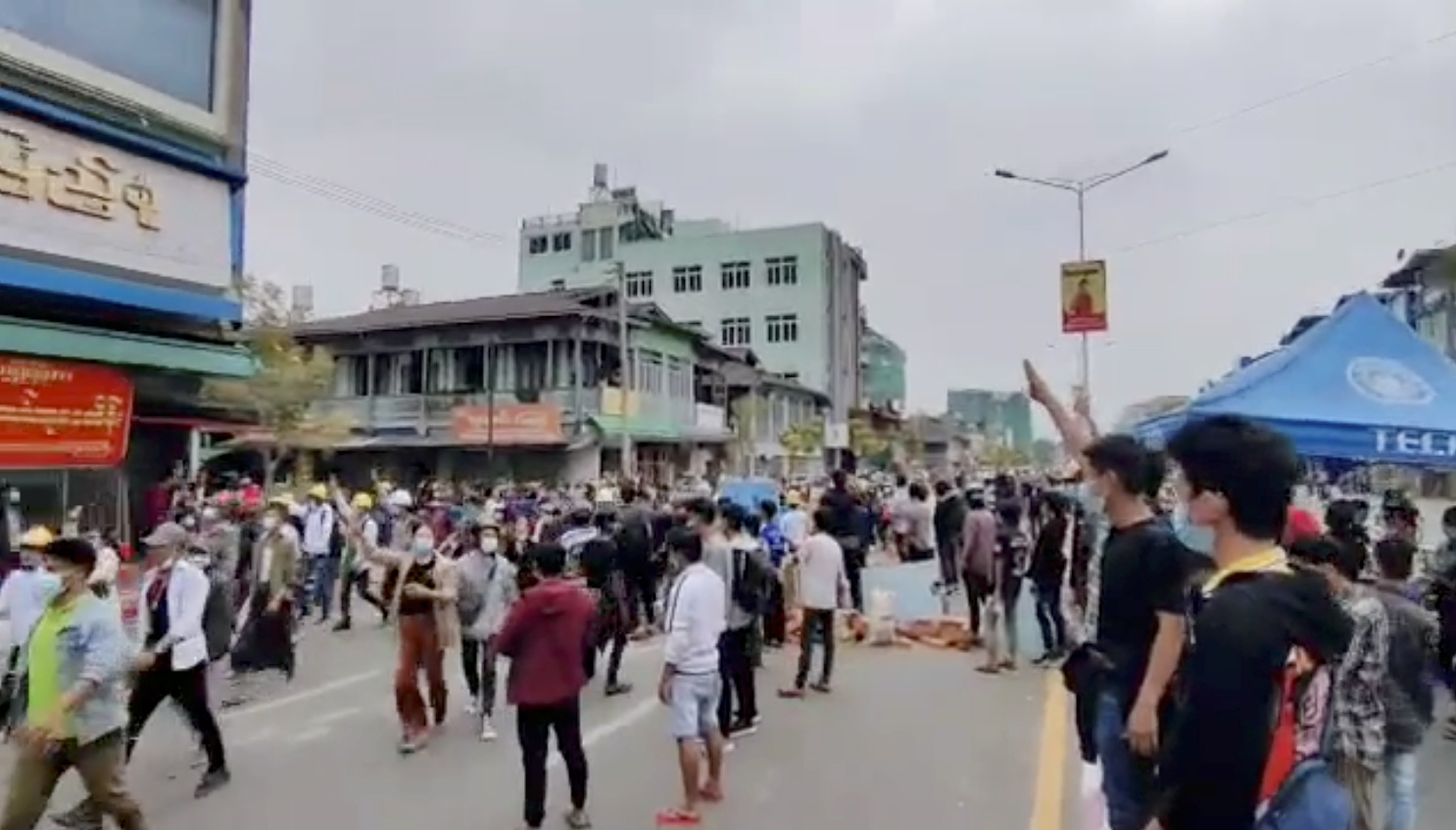 Demonstrators flash three-finger salute during a protest in Myitkyina, Myanmar March 8, 2021 in this still image obtained by Reuters from a video.