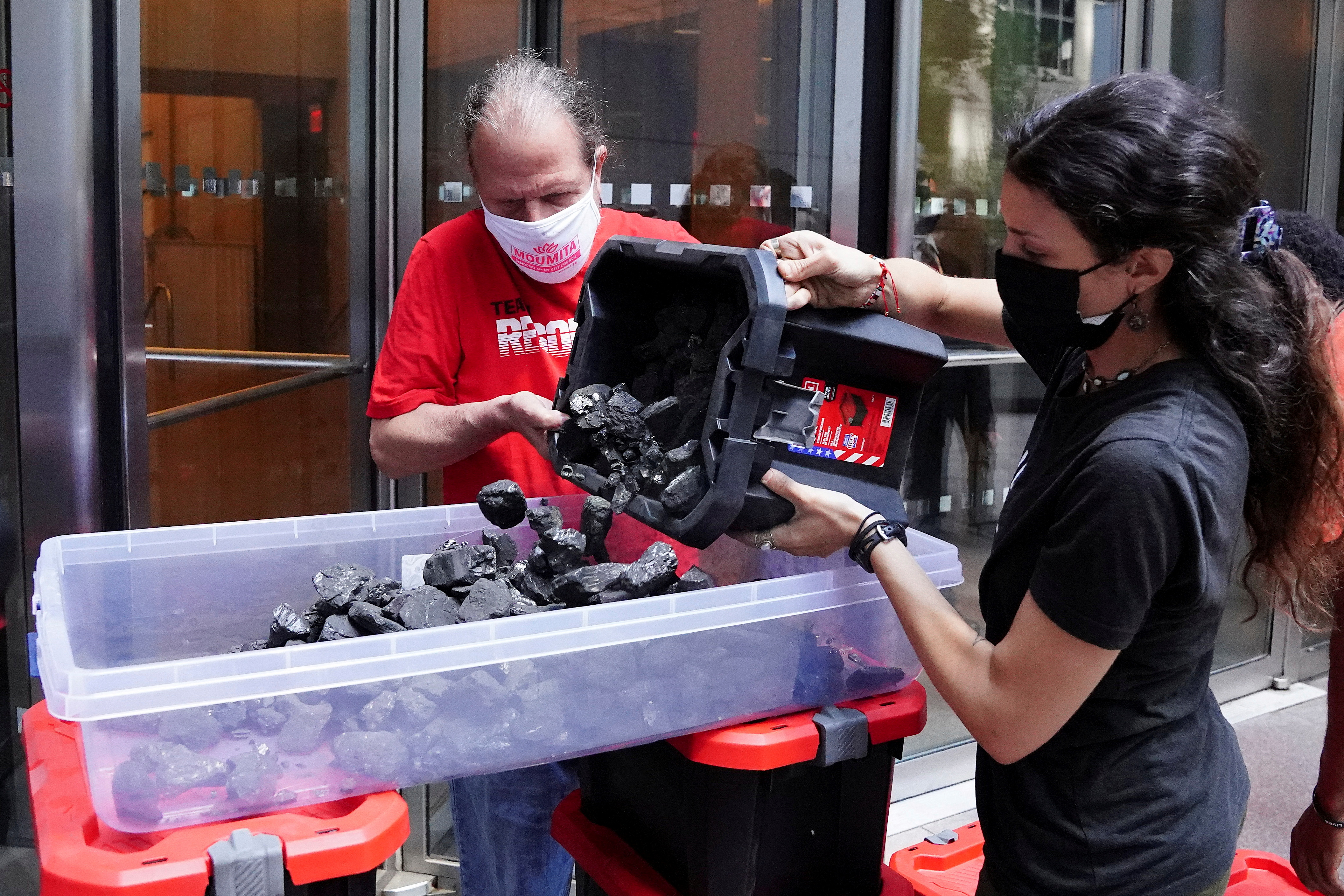 People put coal in a container as they protest against BlackRock investing in coal and tar sands by blocking their front door with coal at their headquarters in the Manhattan borough of New York City, New York, U.S., May 25, 2021.  REUTERS/Carlo Allegri/File Photo