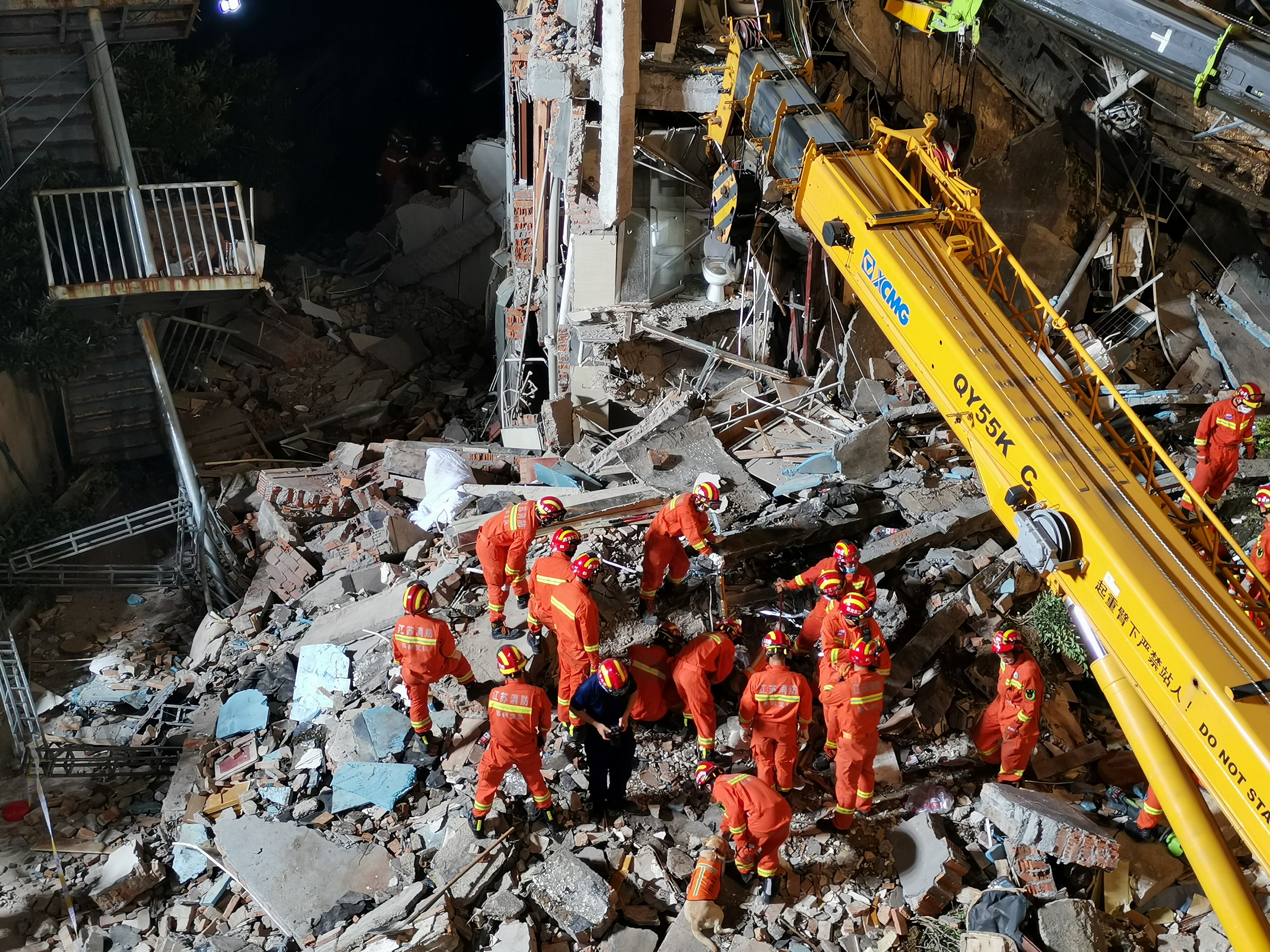 Rescue workers work next to a crane at the site where a hotel building collapsed in Suzhou, Jiangsu province, China July 12, 2021.cnsphoto via REUTERS