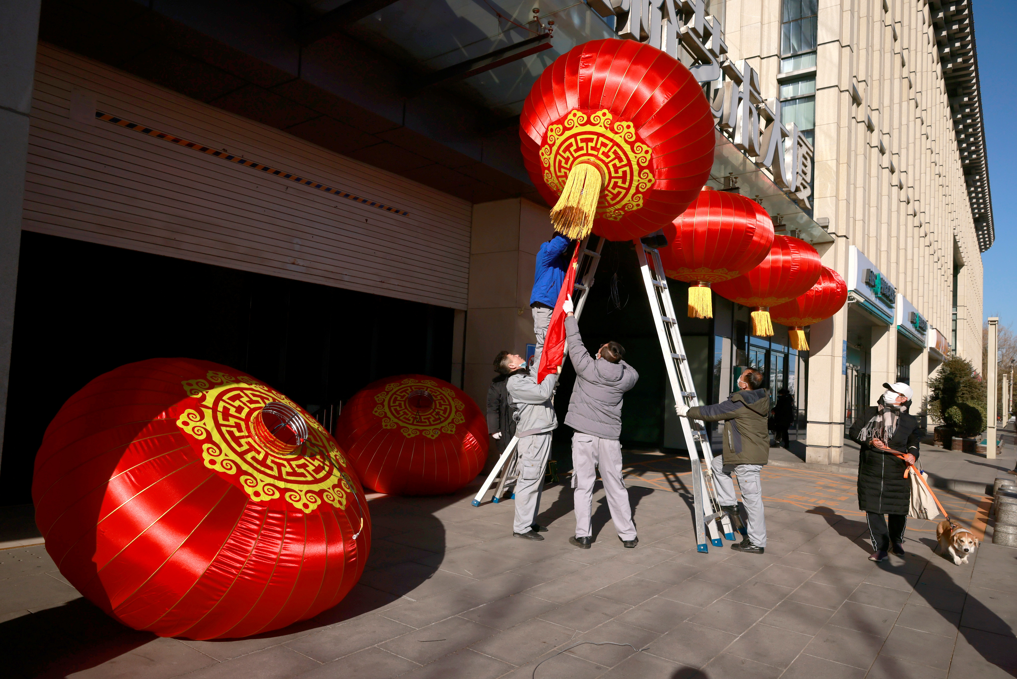 Men hang red lanterns marking New Year and Lunar New Year festivities following the outbreak of the coronavirus disease (COVID-19) in Beijing, China December 31, 2020. REUTERS/Thomas Peter/Files