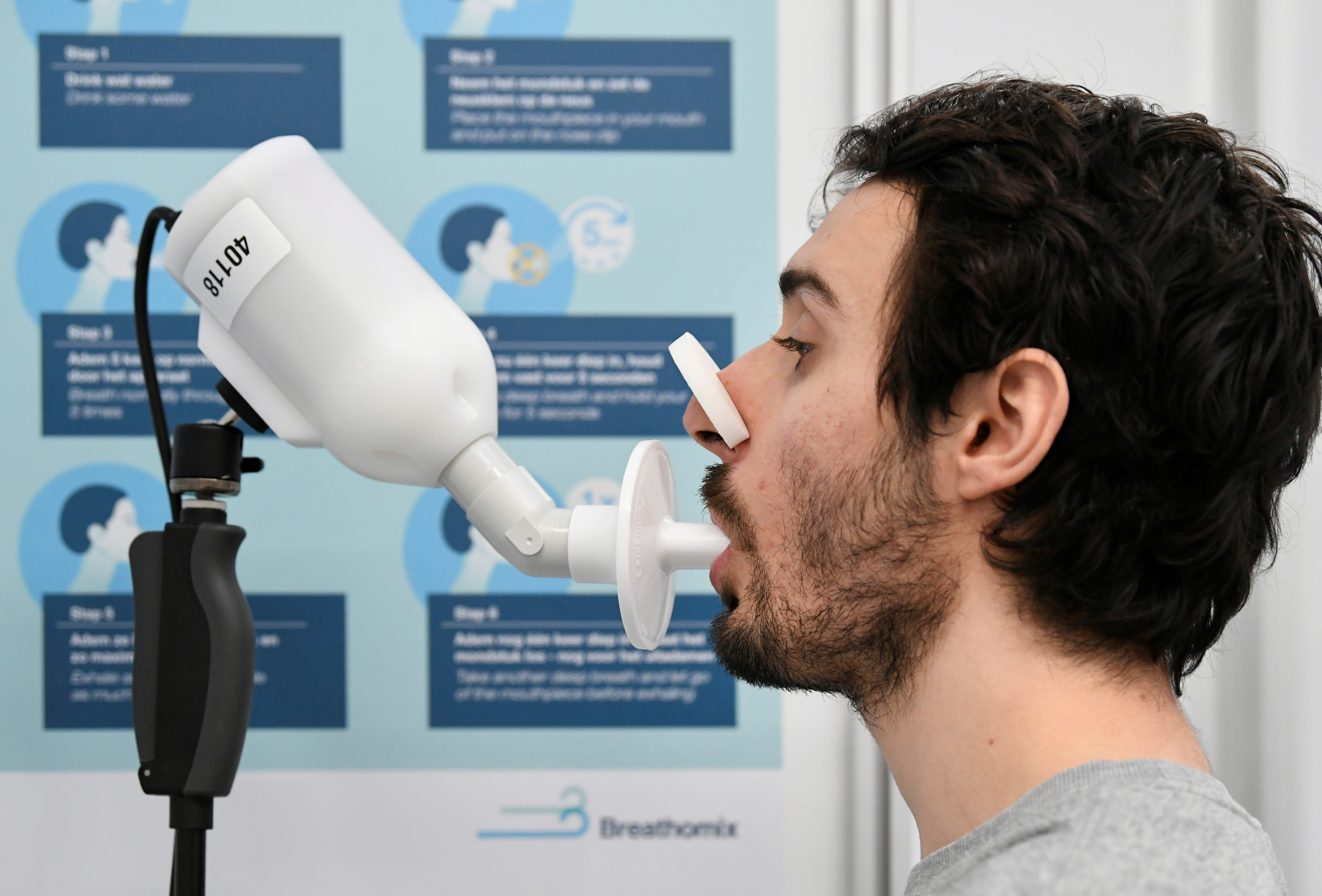 A man demonstrates how a Covid-19 breath test works as the coronavirus disease (COVID-19) testing facilities in the Netherlands will in the coming months be equipped with breath tests capable of giving immediate results, to speed up testing and make it less intrusive in Amsterdam, Netherlands February 1, 2021. Picture taken February 1, 2021. REUTERS/Piroschka van de Wouw